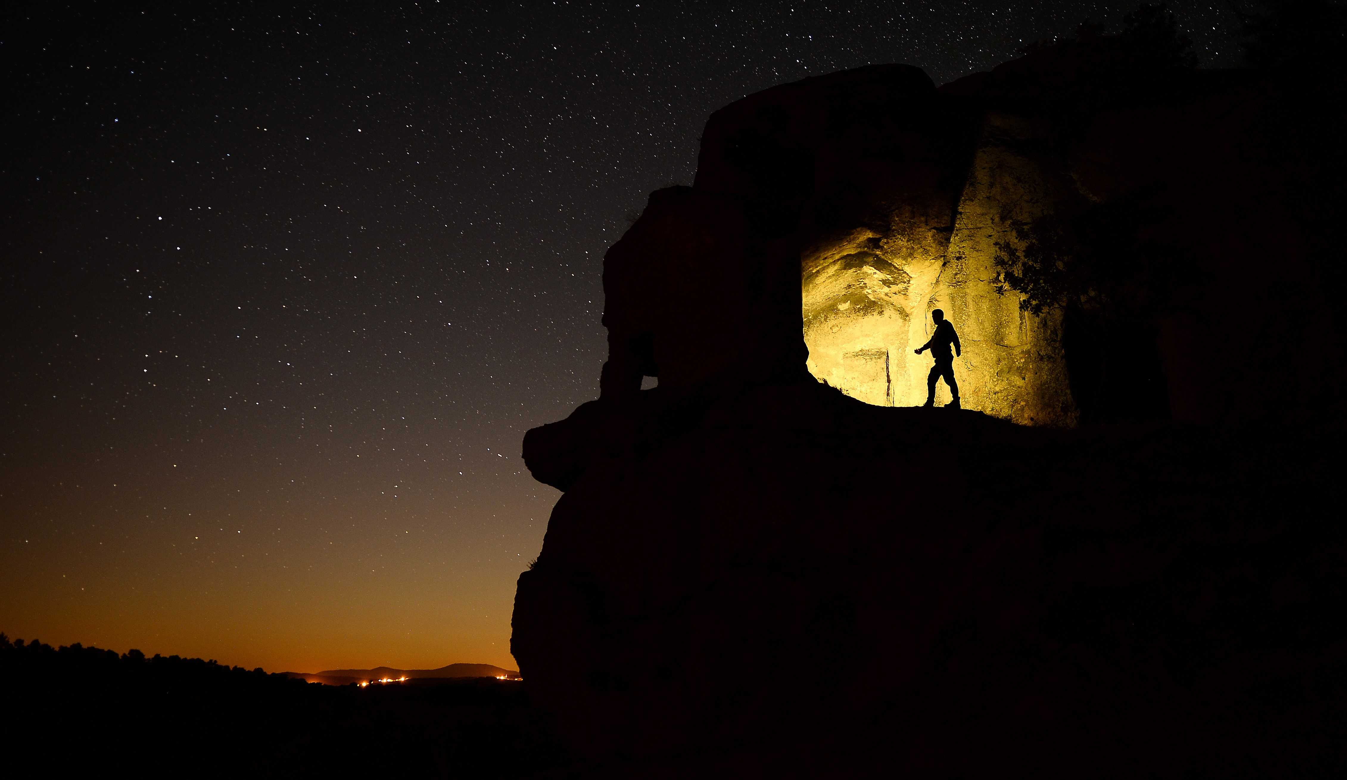 Silhouette of a man standing on a rock outcropping with a clear night sky over the ancient city of Mesotimolos in Turkey, August 13, 2019.