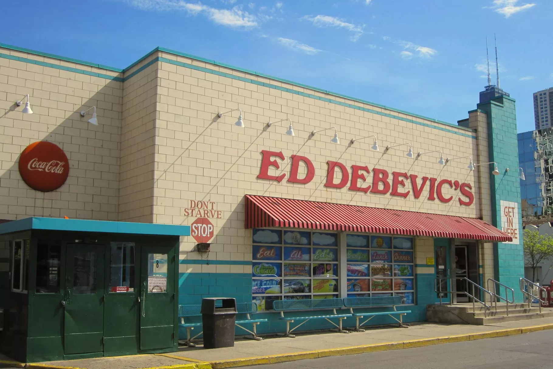 "A large cream-colored brick building with red awning and in red letters ""Ed Debevic's."""