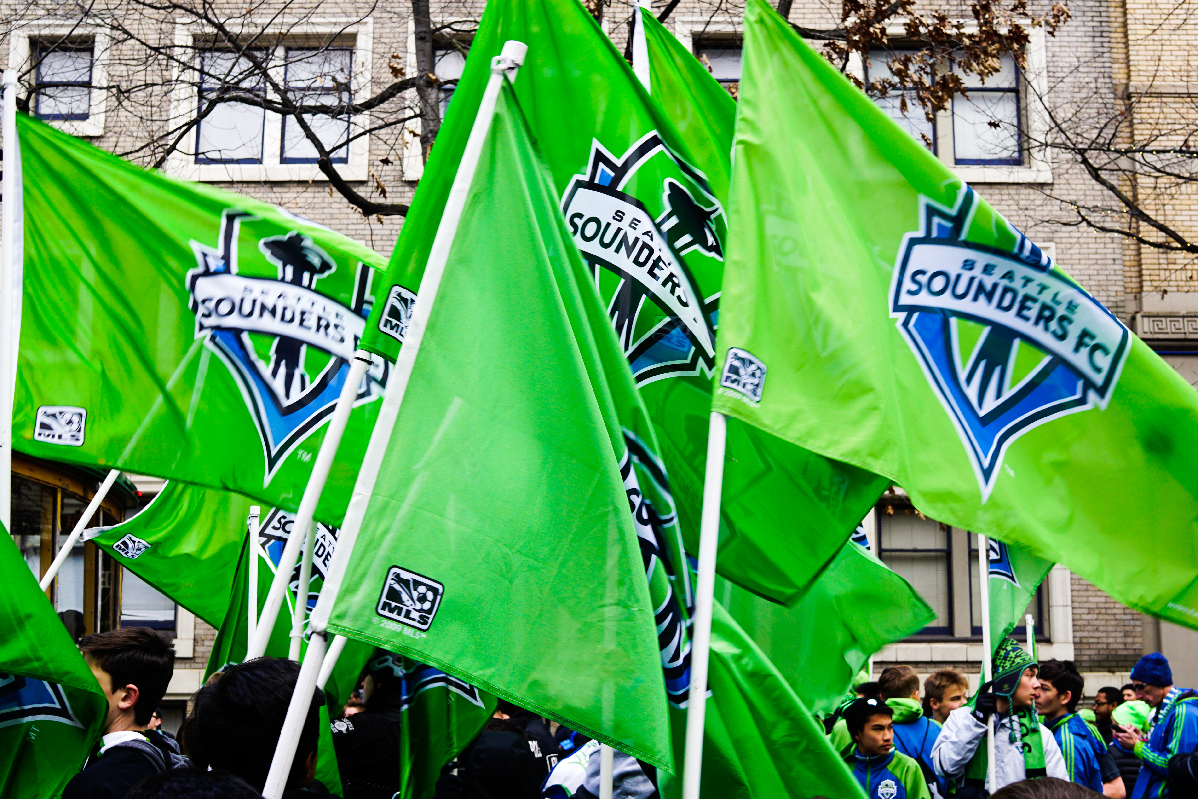 A collection of bright green Seattle Sounders flags, displaying the team's logo prominently.