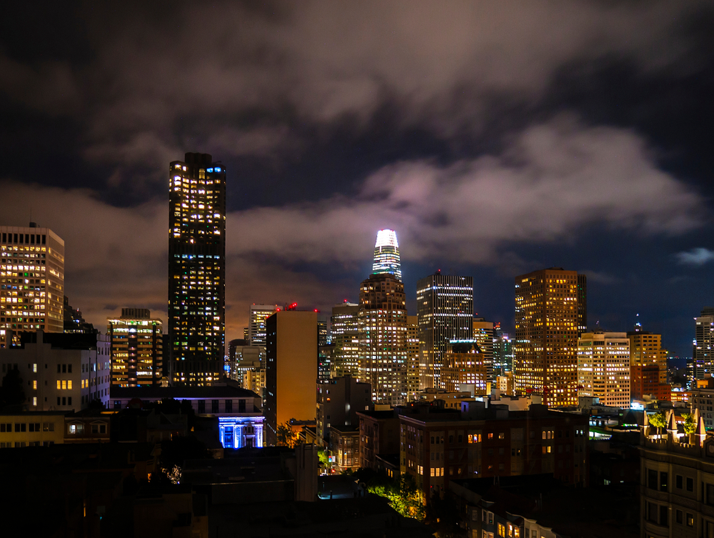 Dark clouds in the night sky over a row of tall buildings.