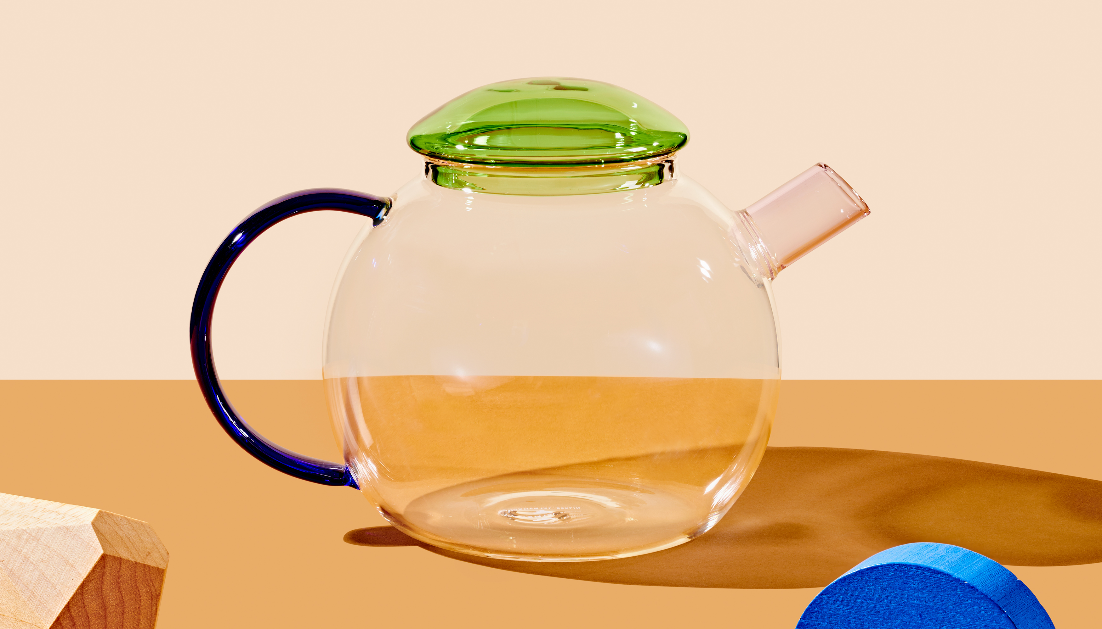 A round shaped clear glass teapot with a clear green lid and a thin, geometric dark blue handle.