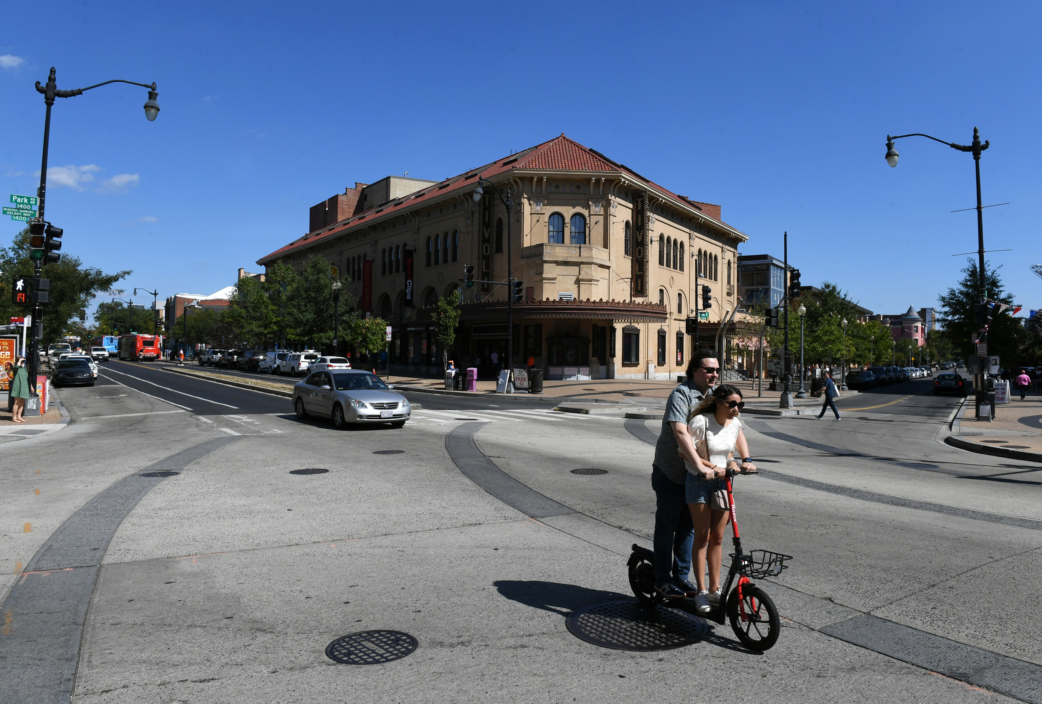 A couple rides an electric scooter through a city intersection. An old theater building stands in the background.