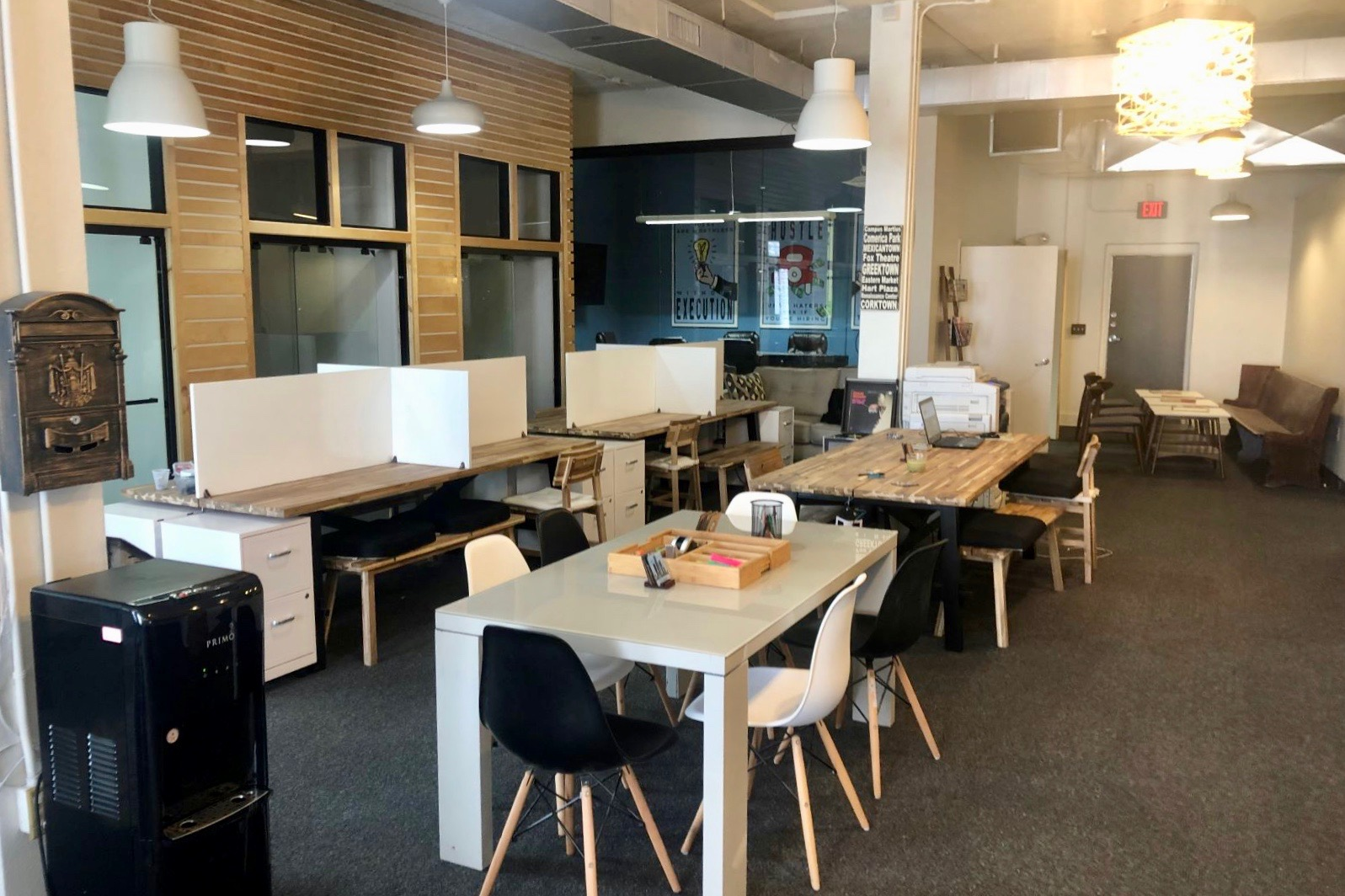 Four desks with chairs around them and some have dividers.