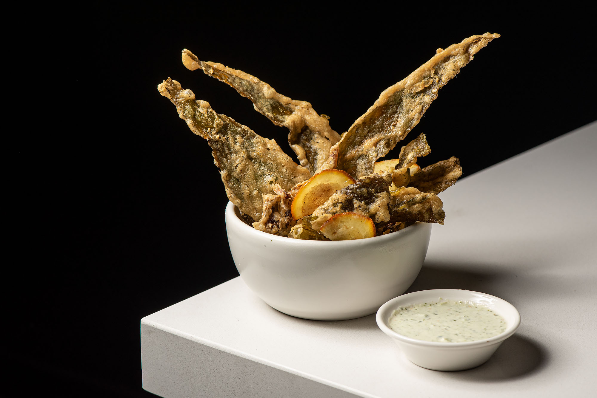 A bowl is filled with spiky pieces of fried kelp, along with a lemon slide, with a dipping sauce.