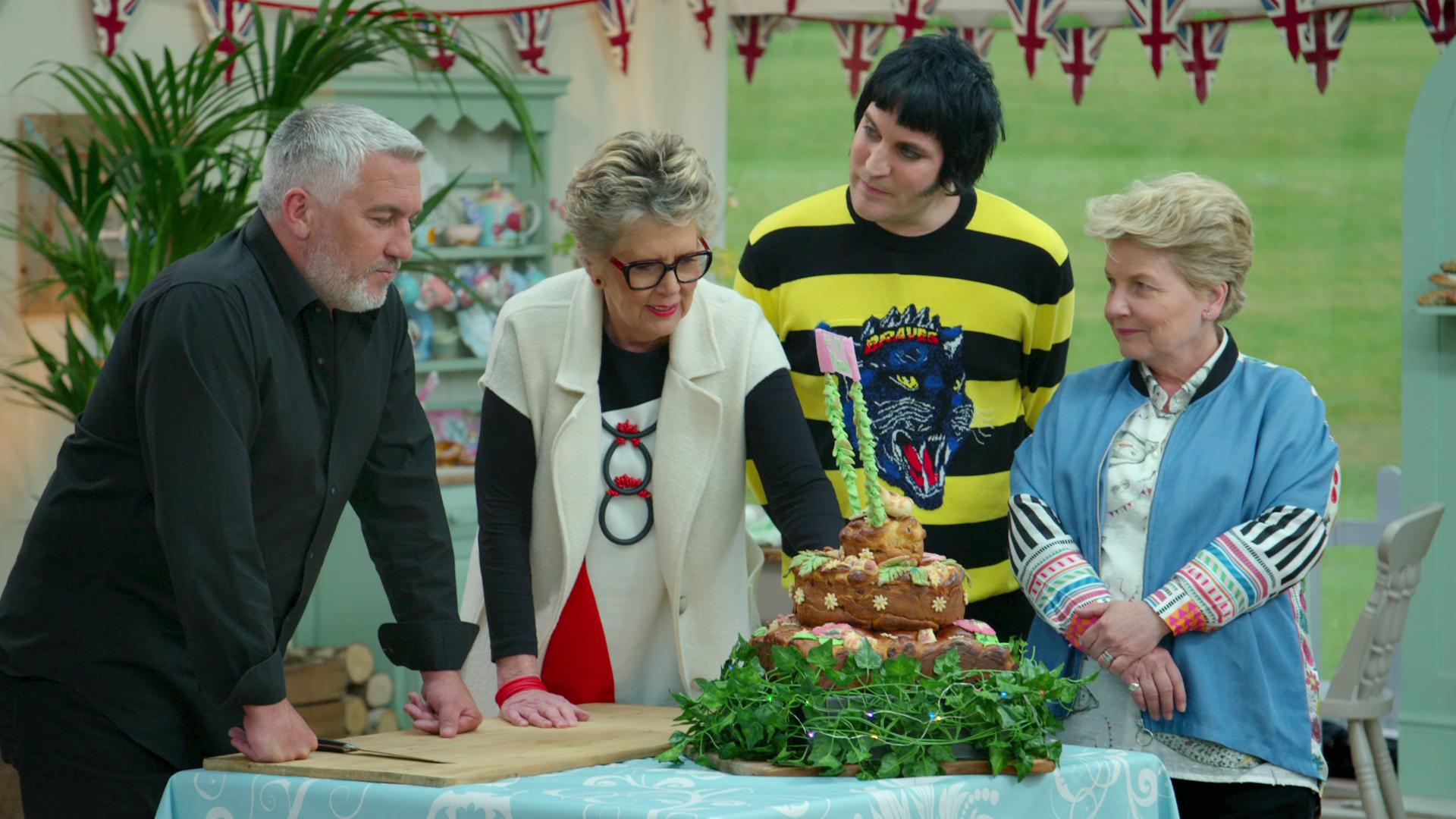 Great British Bake Off's Paul, Prue, Noel, and Sandi examine a festive bread cake creation.