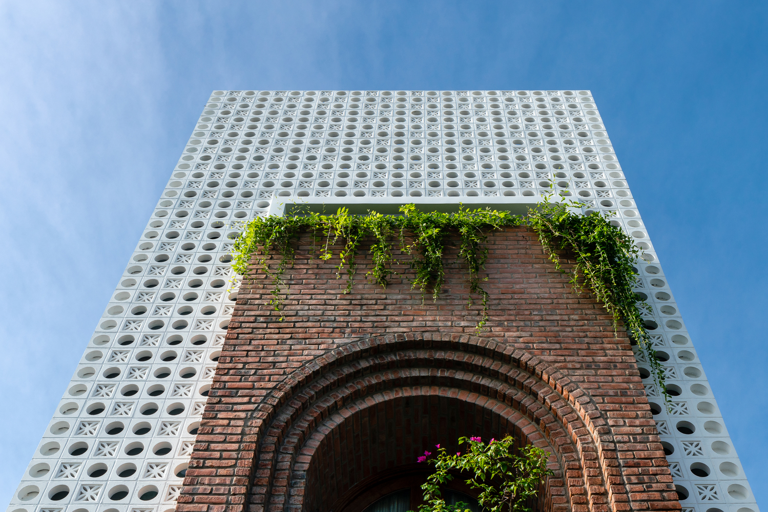 A three-story building boasts a white perforated facade and a brick arch for the entrance.
