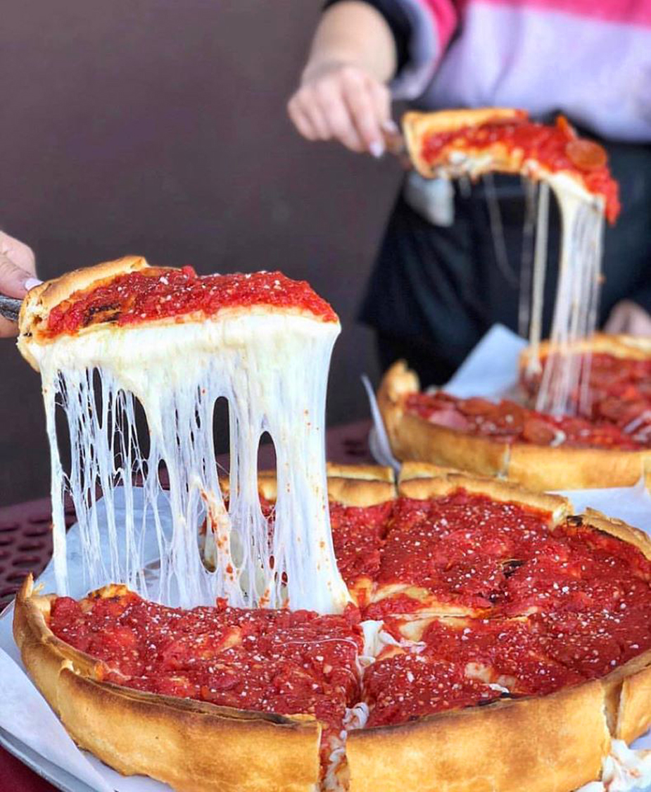 Two servers demonstrate the cheese pull of the deep dish pizza at Amore Taste of Chicago.