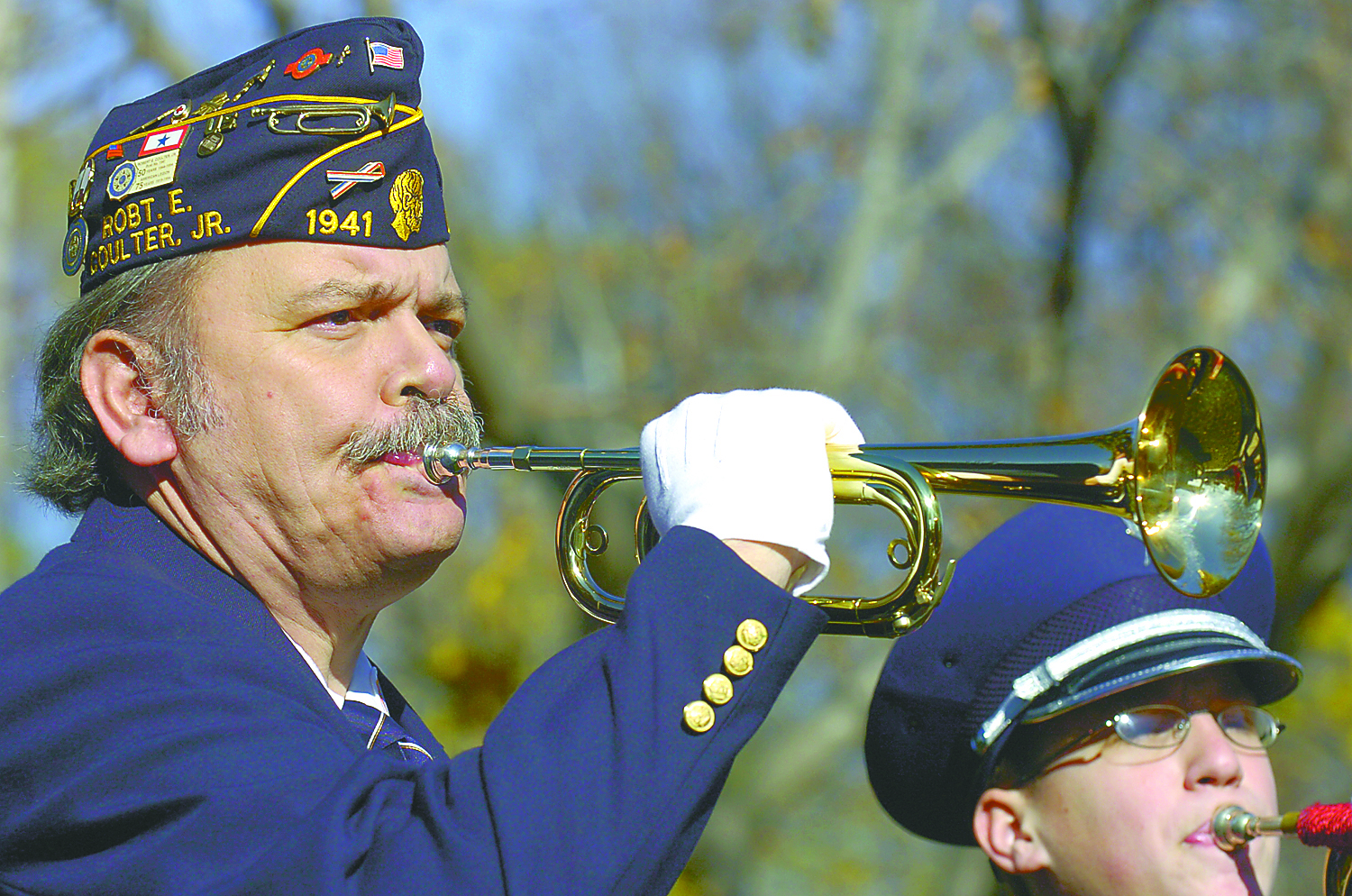 Man blows bugle at Veterans Day ceremony