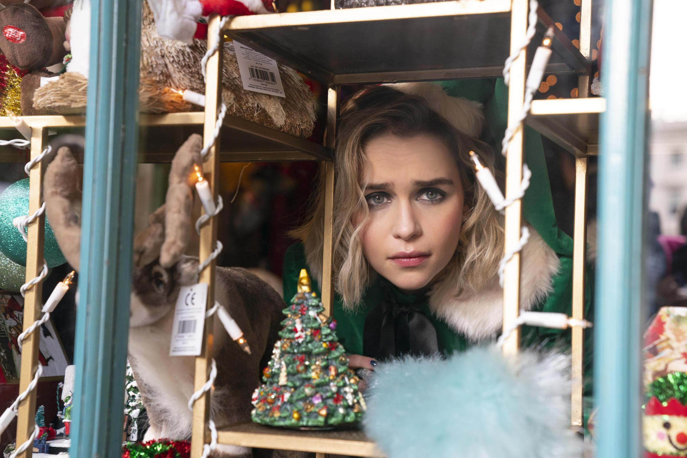 Emilia Clarke as Kate, peering through a window.