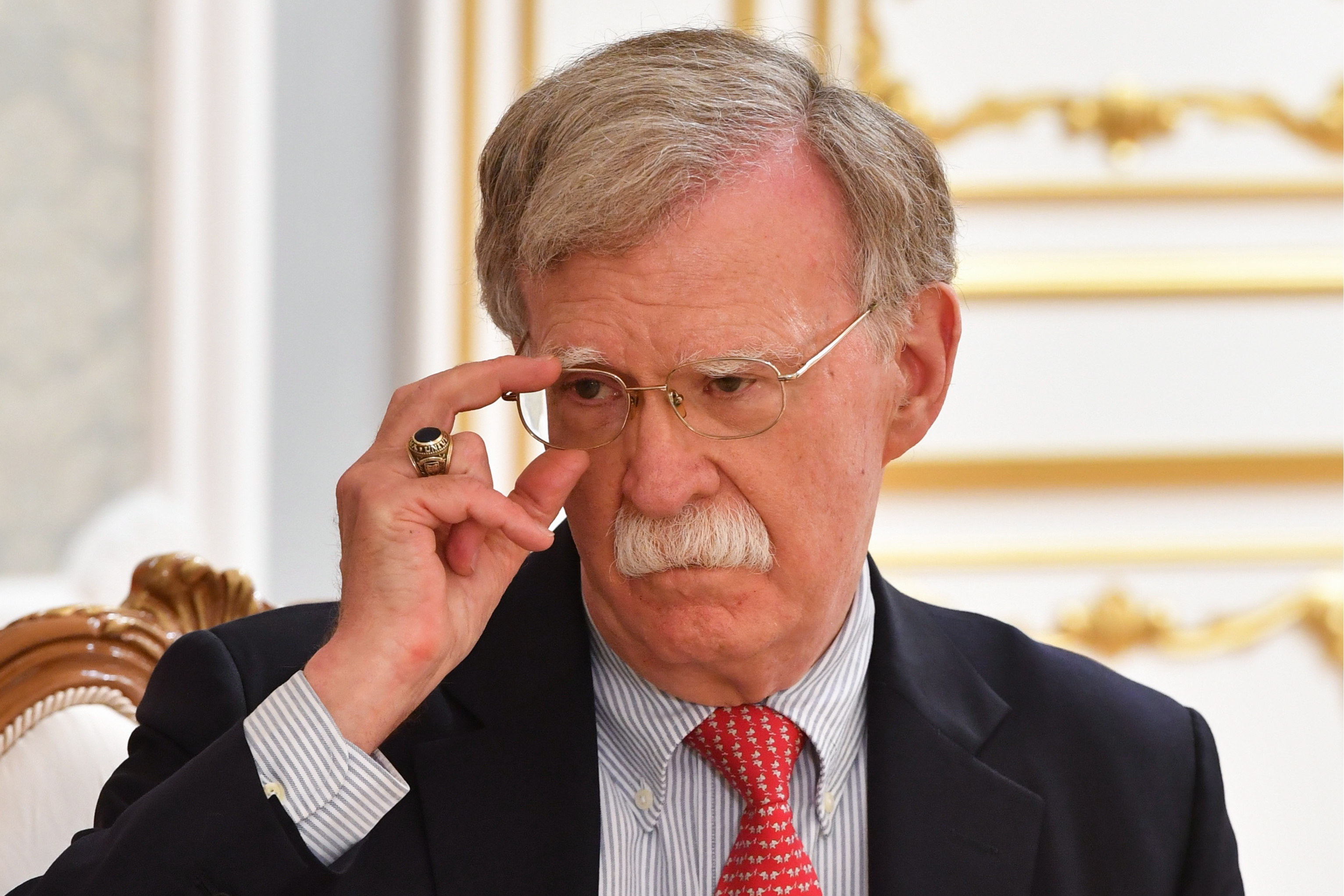 US National Security Adviser John Bolton adjusts his glasses and looks skeptical. Taken during a meeting with Belarus' President Alexander Lukashenko.