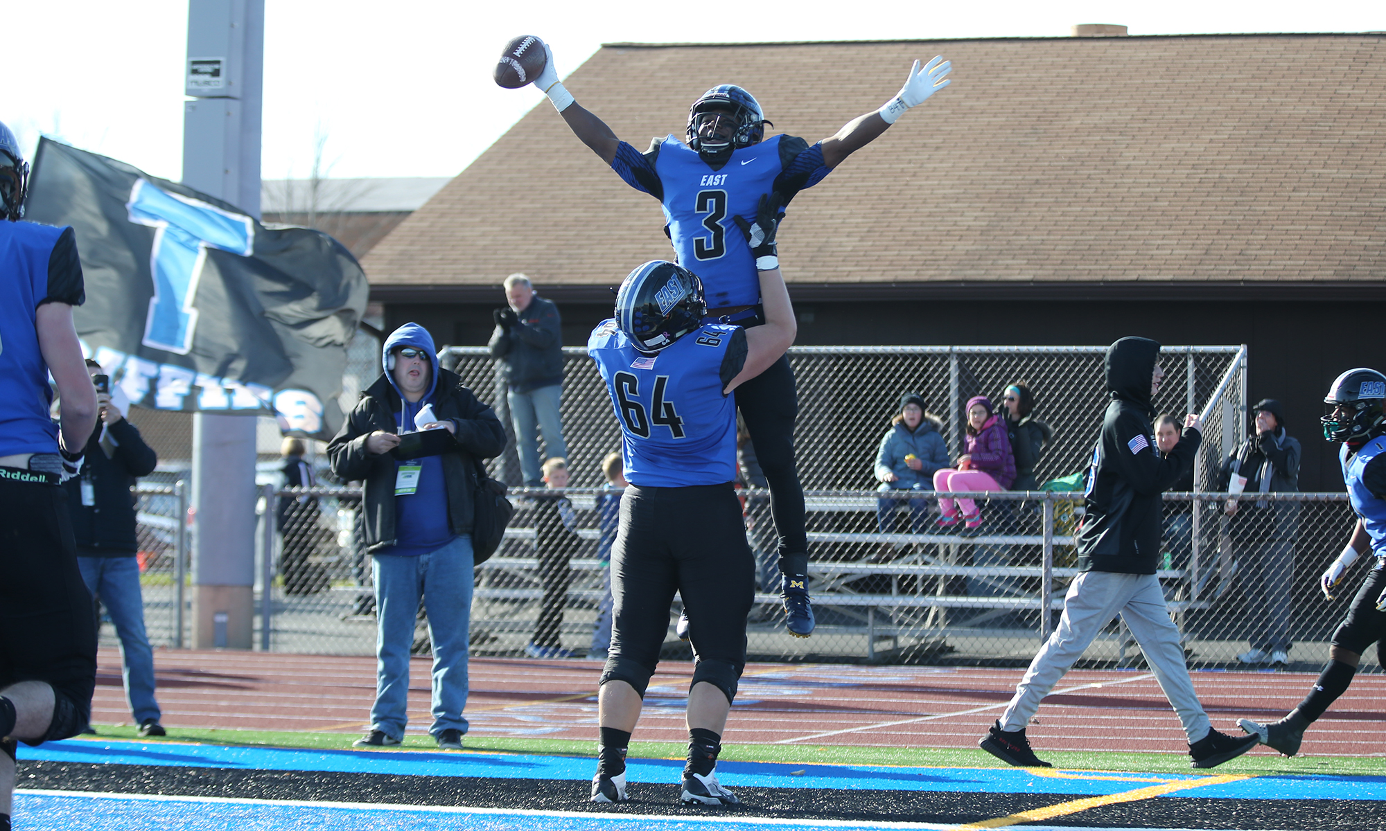 Lincoln-Way East's Alec Ogarek (64) lifts A.J. Henning (3) after Henning score one of his three touchdowns against Notre Dame.