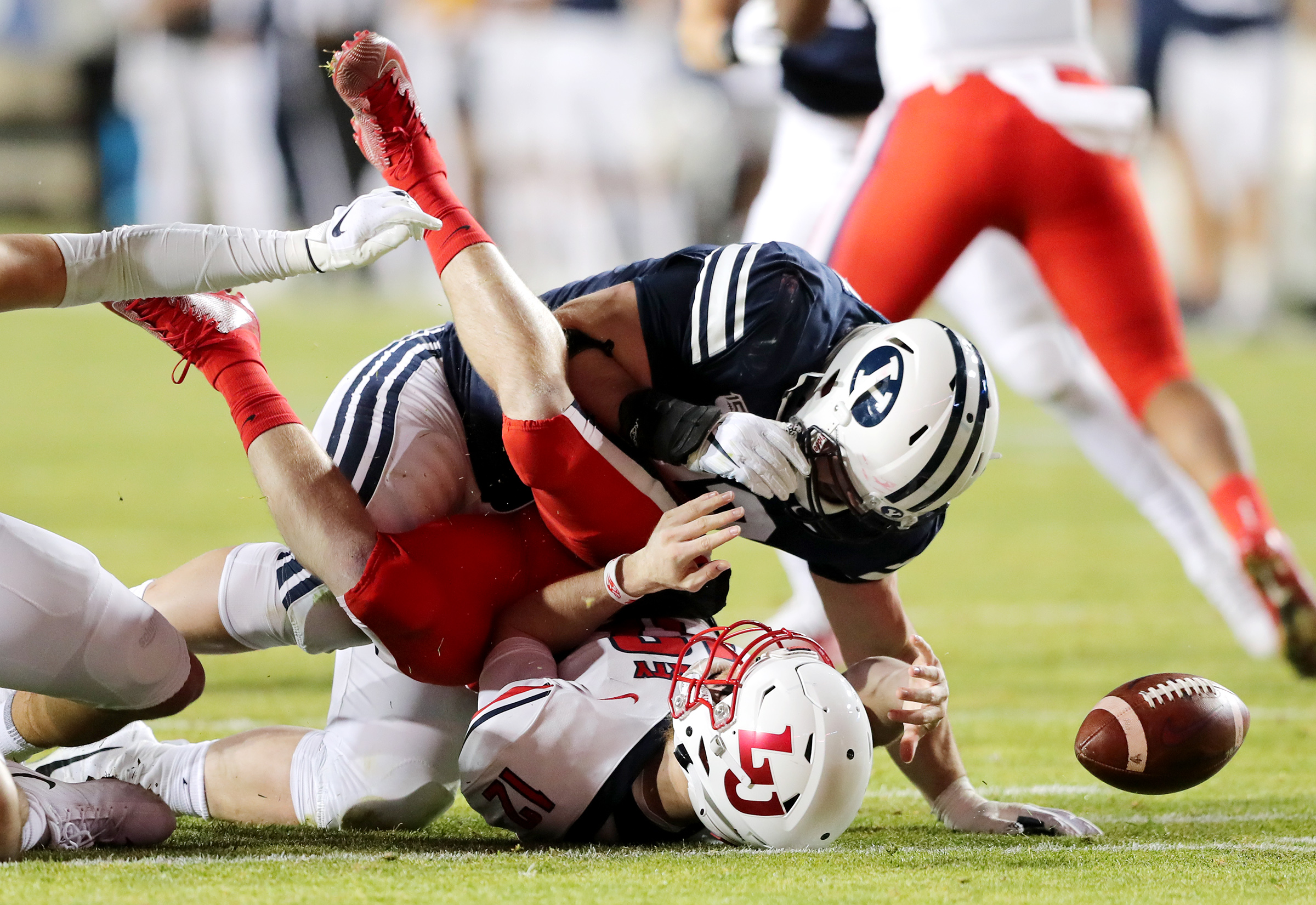 Liberty Flames quarterback Stephen Calvert (12) loses the ball as he is hit by Brigham Young Cougars defensive lineman Bracken El-Bakri (93) after being sacked by Brigham Young Cougars linebacker Keenan Pili (41) as BYU and Liberty play an NCAA football game in Provo, Utah on Saturday, Nov. 9, 2019.