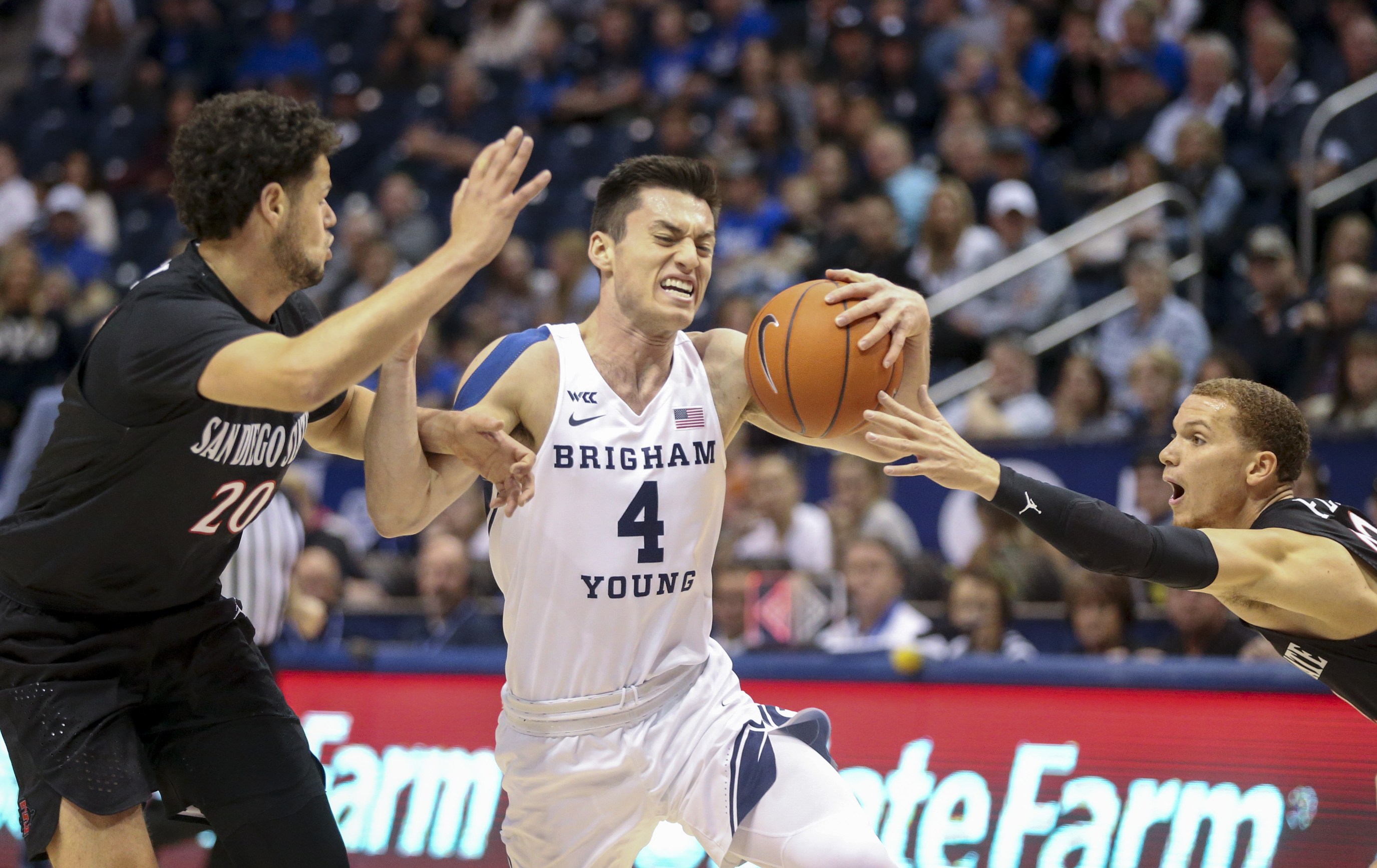 Brigham Young Cougars guard Alex Barcello (4) runs through San Diego State Aztecs guards Jordan Schakel (20) and Malachi Flynn (22) during the first half of an NCAA basketball game at Marriott Center in Provo on Saturday, Nov. 9, 2019.