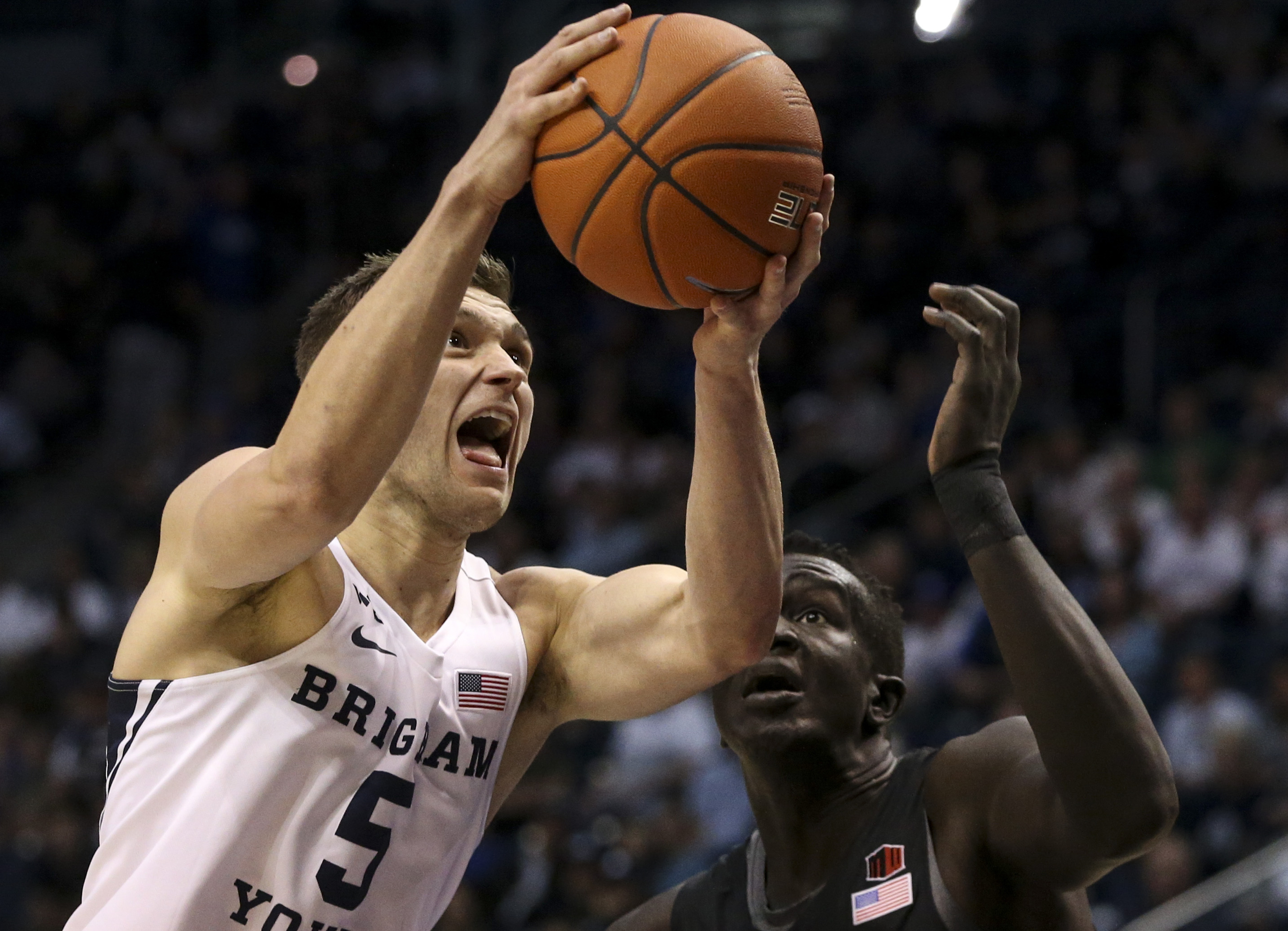 Brigham Young Cougars guard Jake Toolson (5) goes to the basket while defended by San Diego State Aztecs forward Aguek Arop (3) during the first half of an NCAA basketball game at Marriott Center in Provo on Saturday, Nov. 9, 2019.