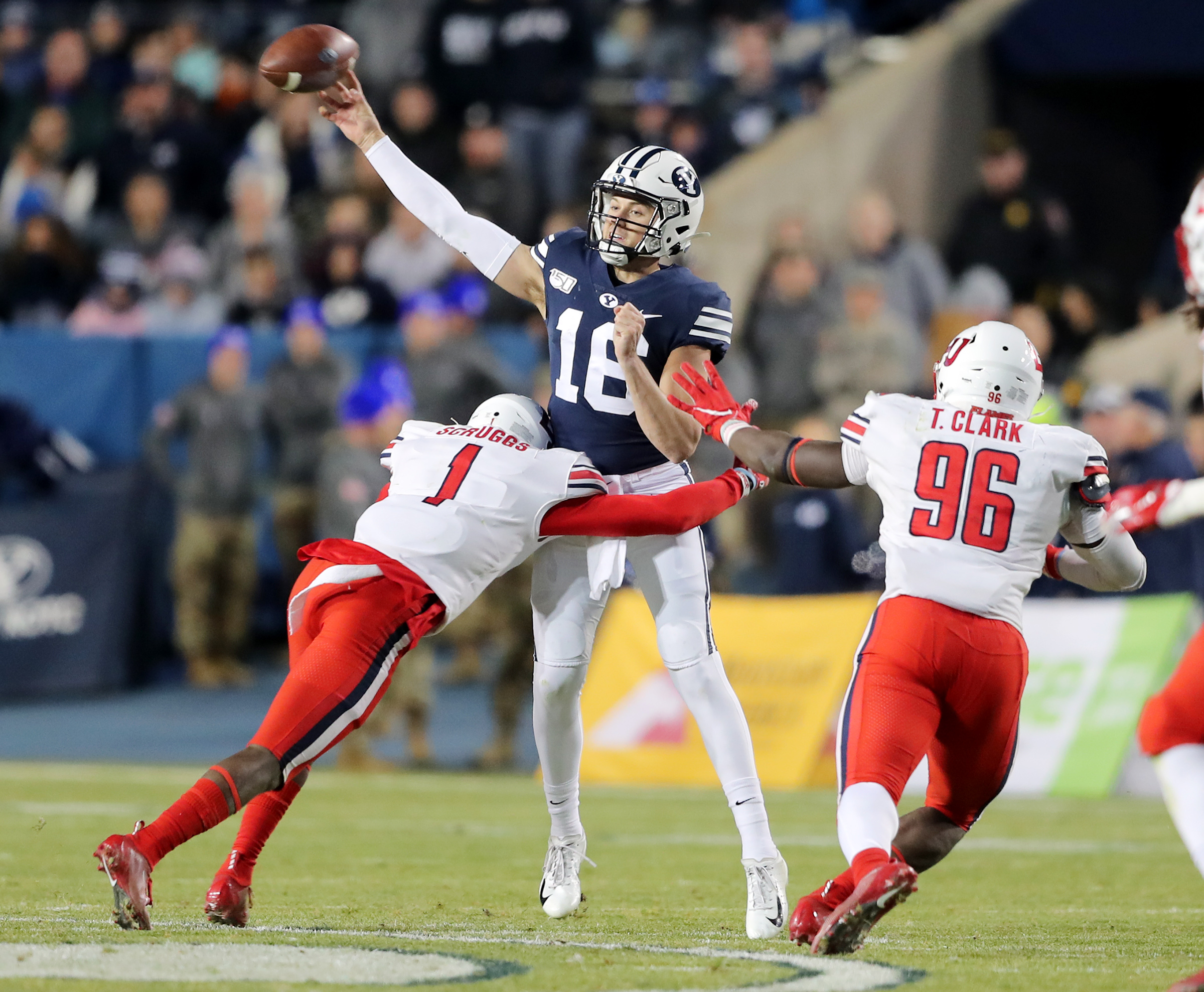 Brigham Young Cougars quarterback Baylor Romney (16) throws the ball as he is hit by Liberty Flames cornerback Javon Scruggs (1) BYU and Liberty play an NCAA football game in Provo, Utah on Saturday, Nov. 9, 2019. BYU won 31-24.