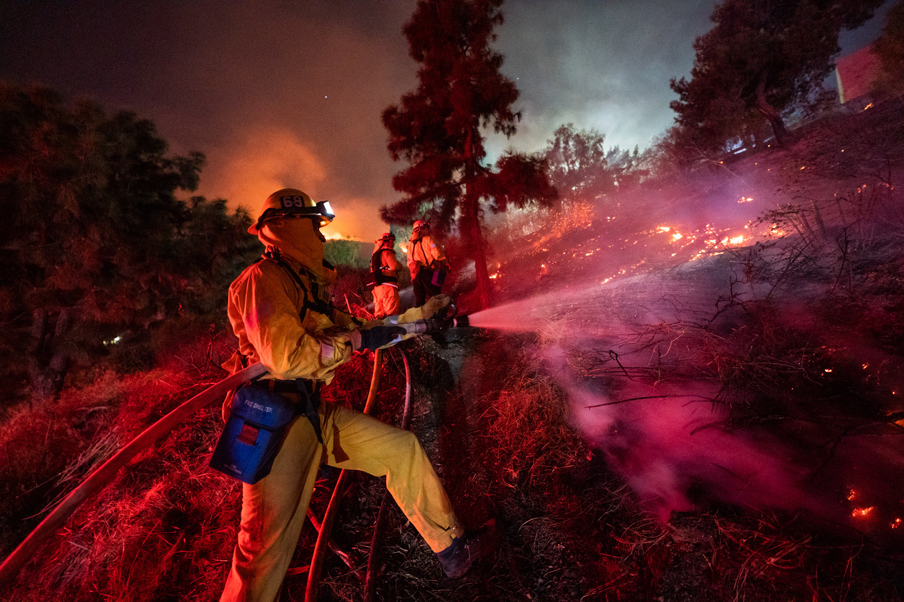 Firefighters work to put out a fire near Getty Center in Los Angeles.