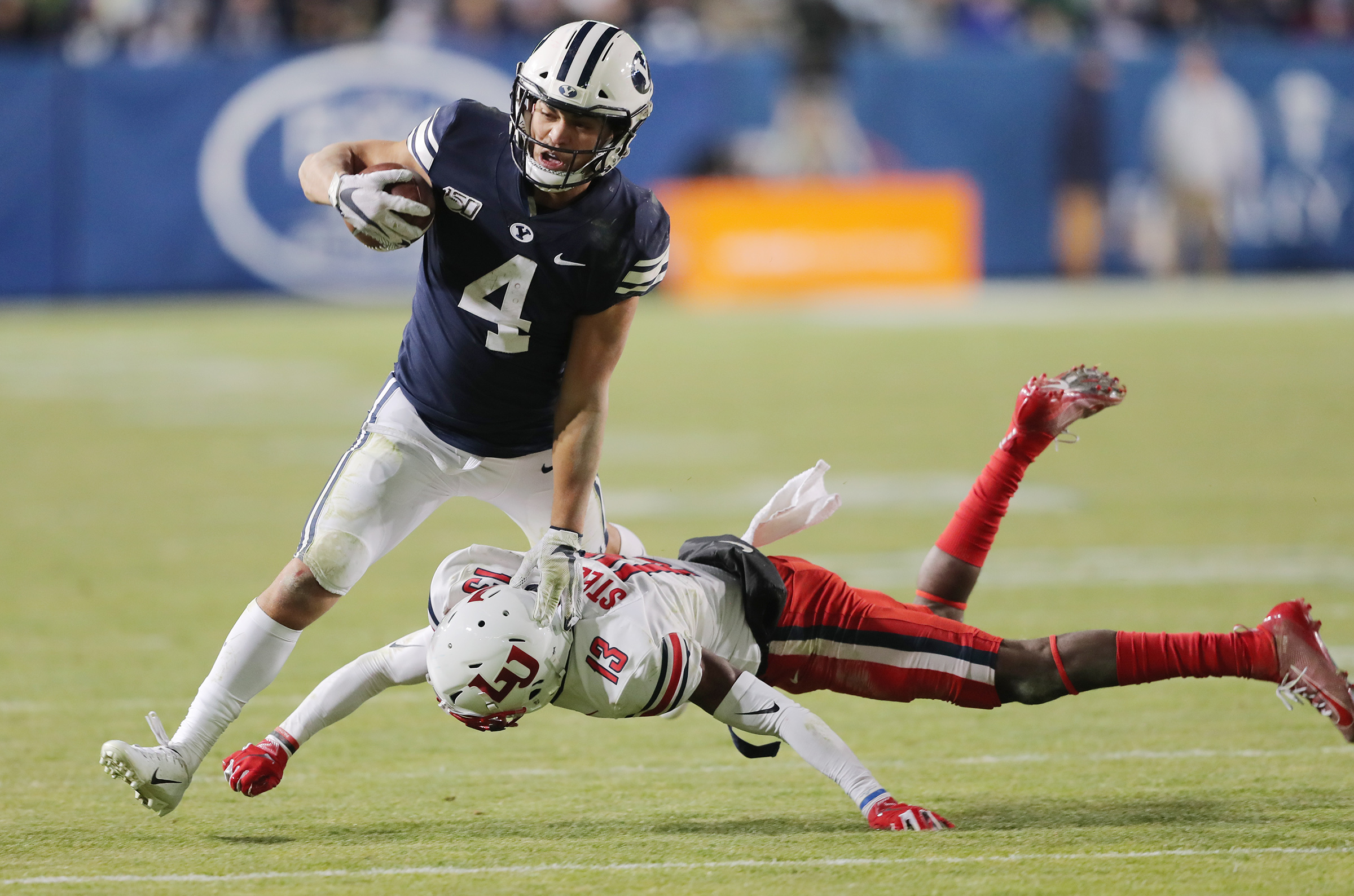 Brigham Young Cougars running back Lopini Katoa (4) is hit by Liberty Flames safety Isaac Steele (13) as BYU and Liberty play an NCAA football game in Provo, Utah on Saturday, Nov. 9, 2019. BYU won 31-24.