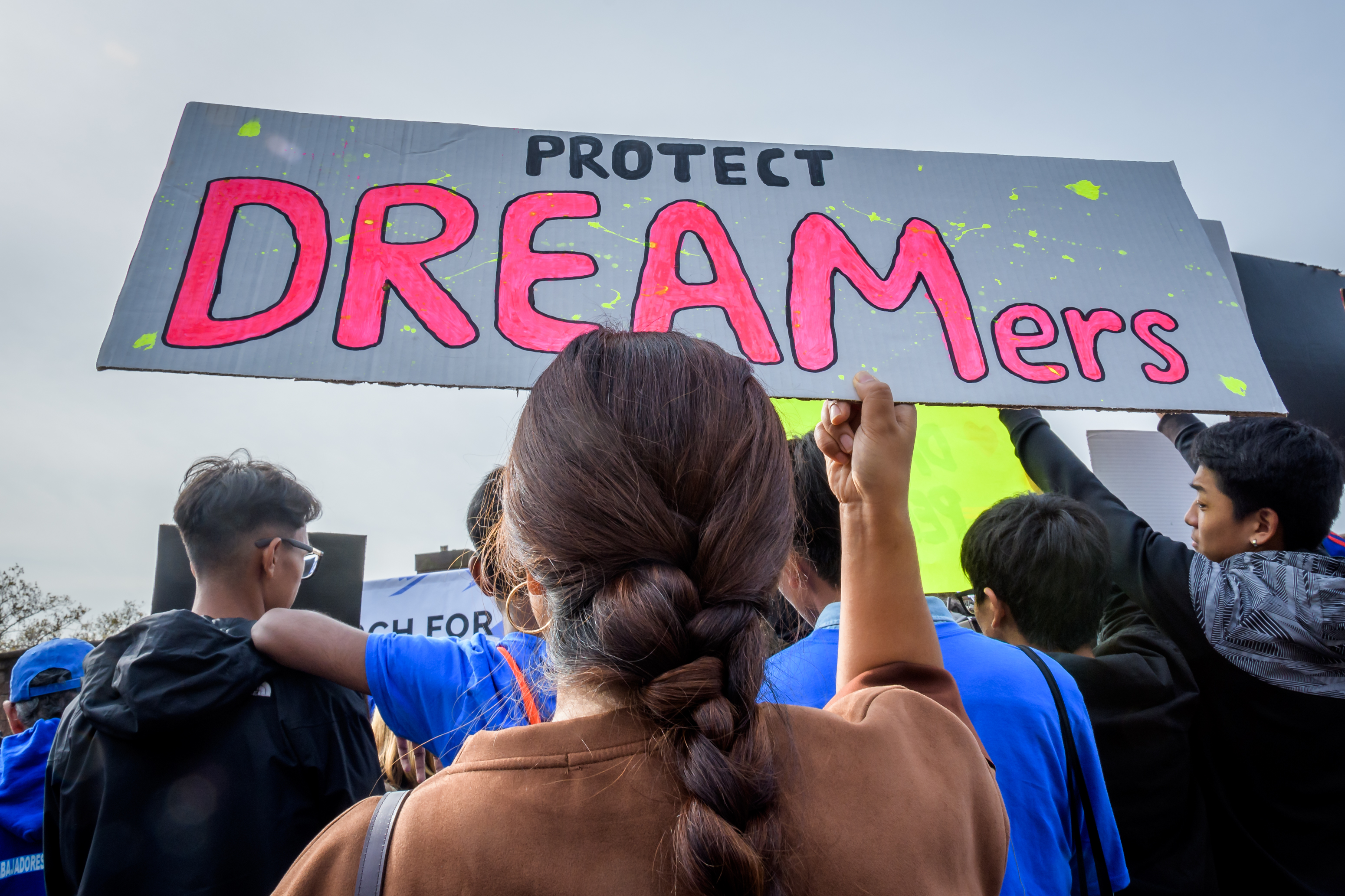 "Protesters carry a sign that reads, ""Protect DREAMers."""