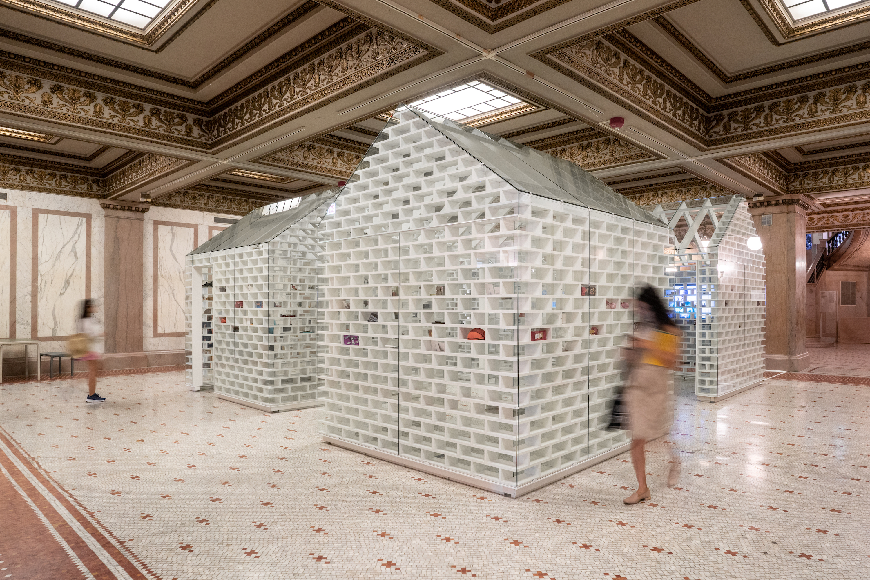 Three tiny houses made from glass bricks inside of a neo-classical building with a tiled floor and coffered ceiling