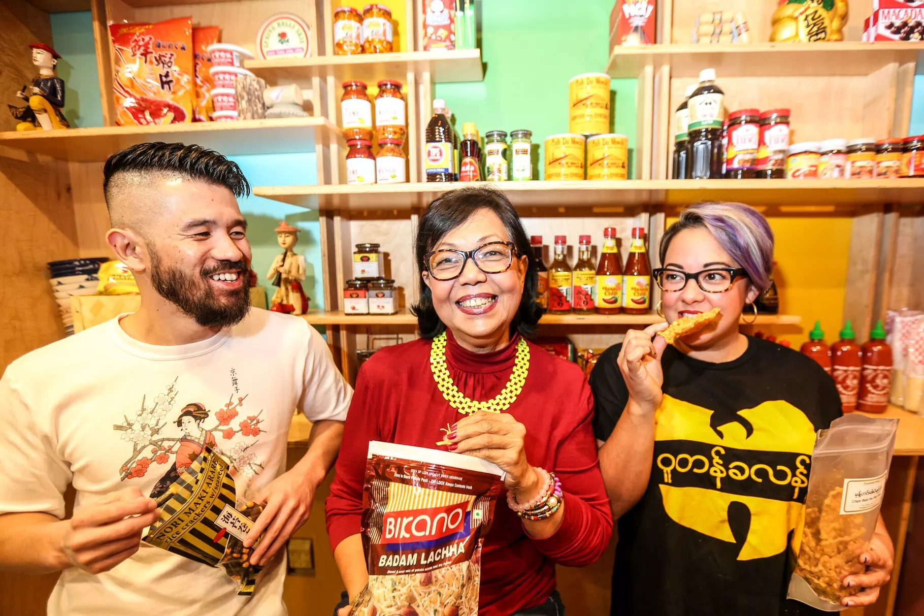 Toli Moli owners, from left, Eric Wang, Jocelyn Law-Yone, and Simone Jacobson hold snacks inside the Burmese bodega