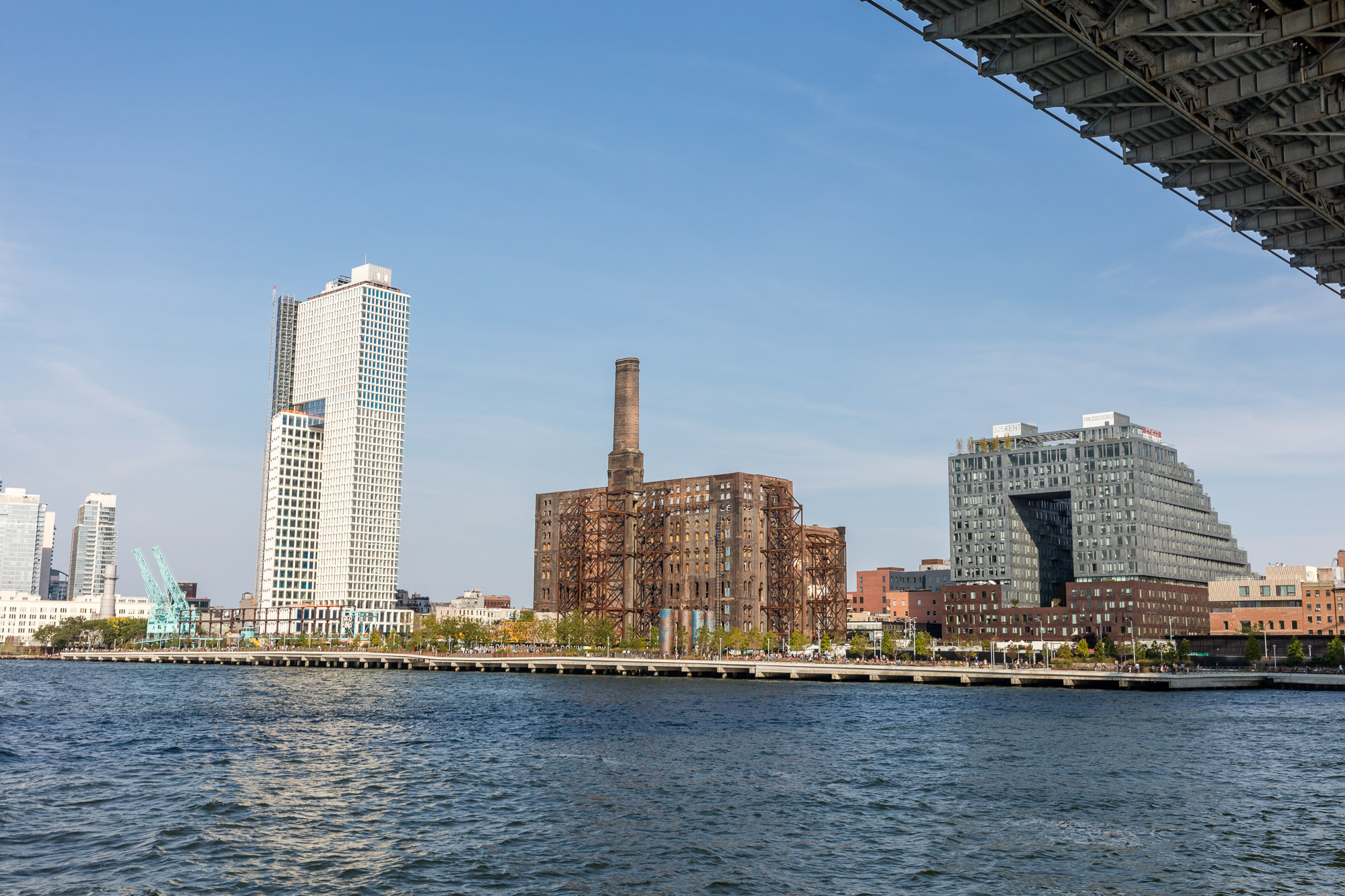 Three buildings stand on a waterfront: One tall white tower, a factory, and a 16-story doughnut-shaped building.