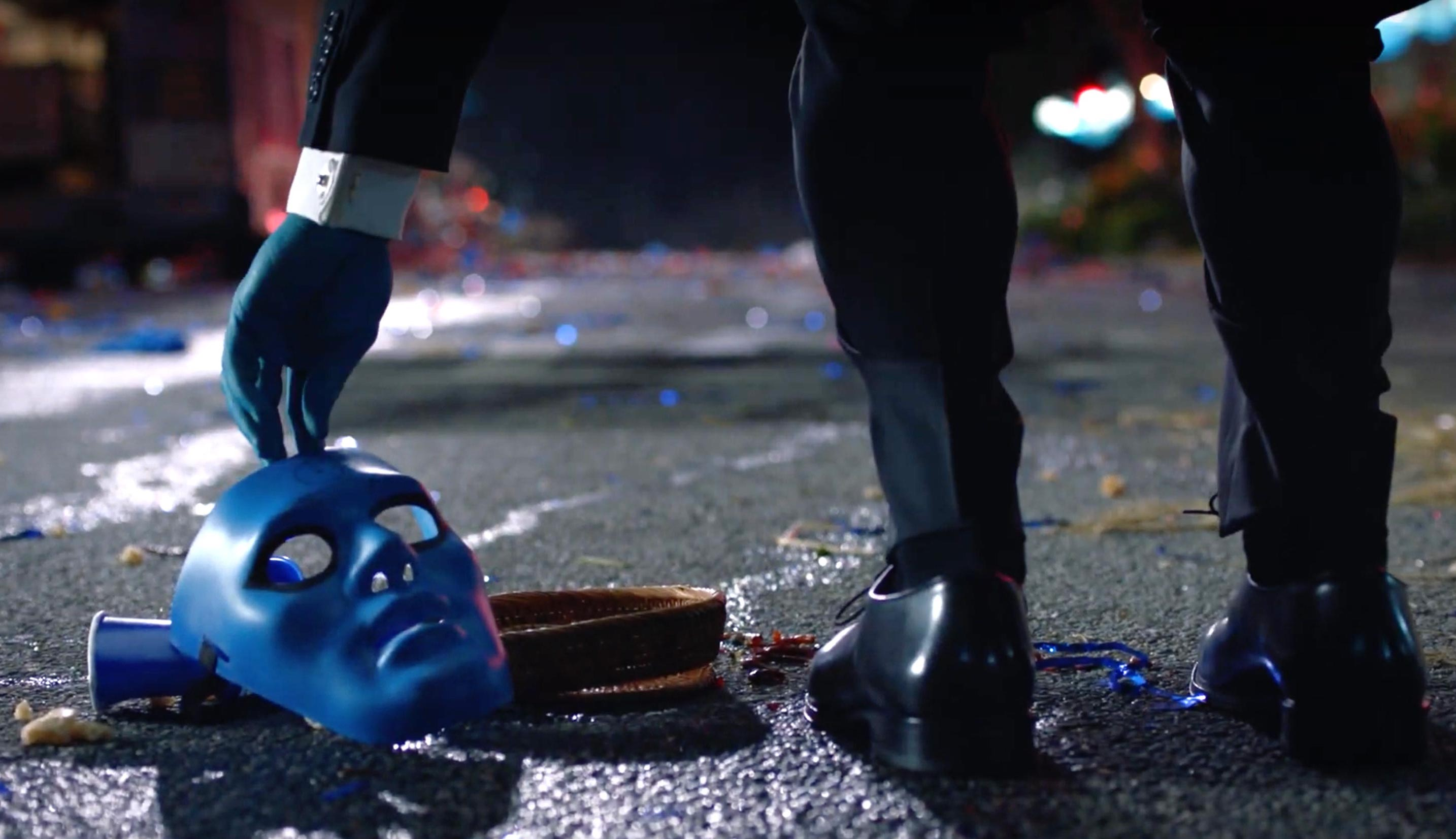 doctor manhattan picks a blue mask off the ground in hbo's watchmen