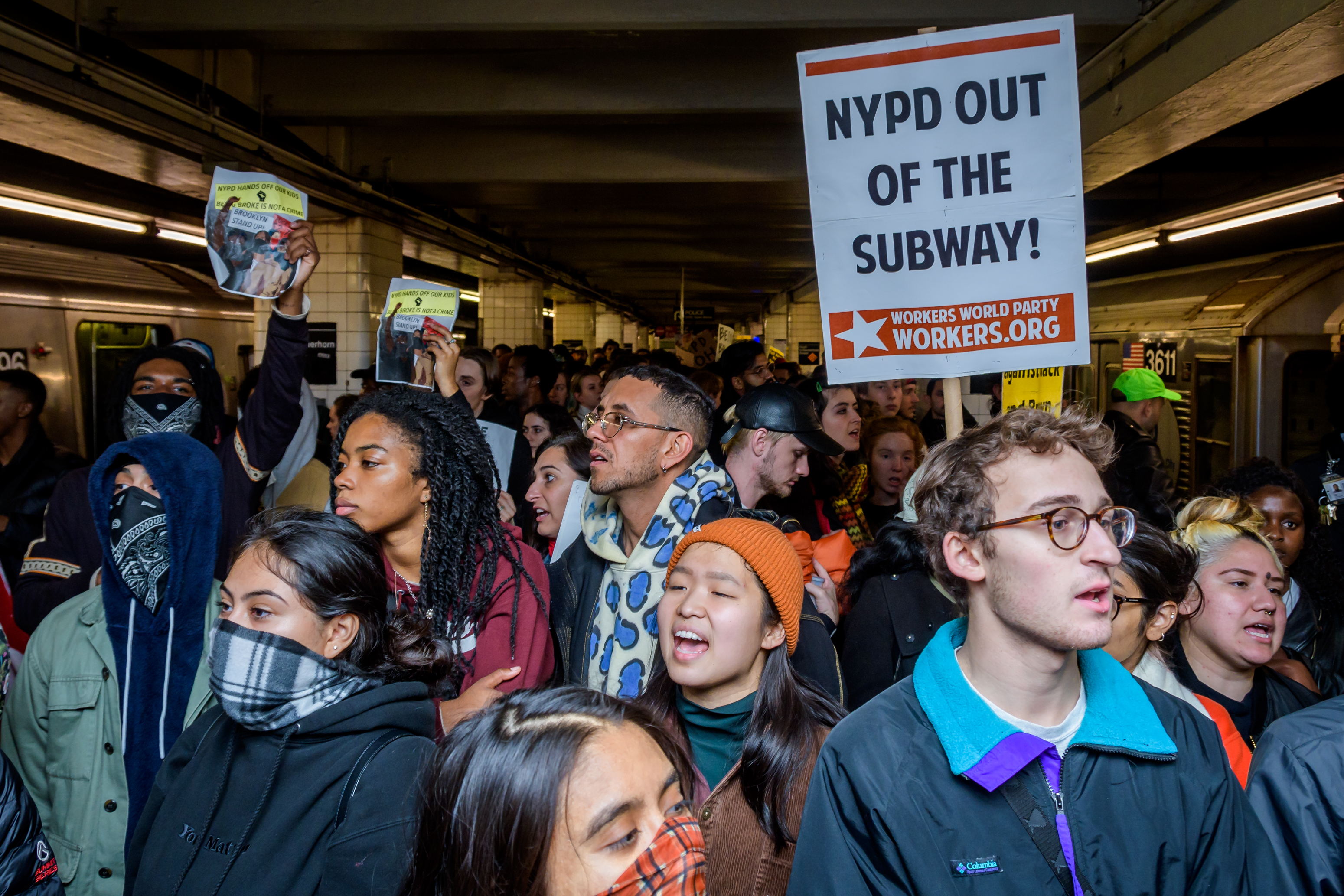 """Dozens of protesters gather on a subway platform with signs, one reading """"NYPD out of the subway."""""""