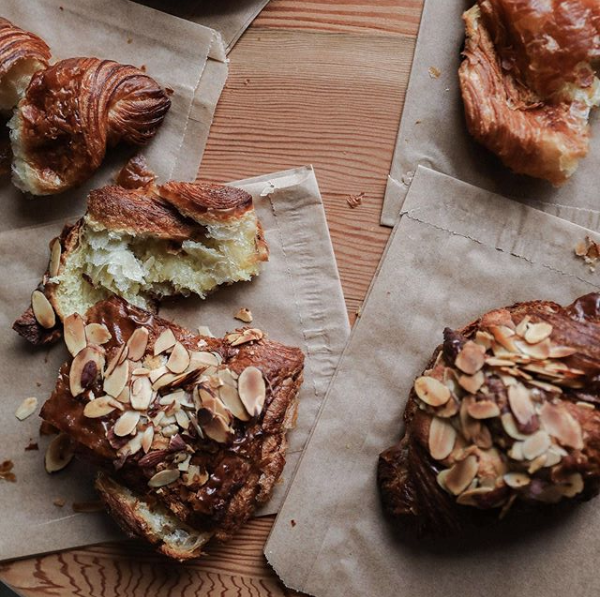 A pile of croissants and assorted pastries with almonds on top.