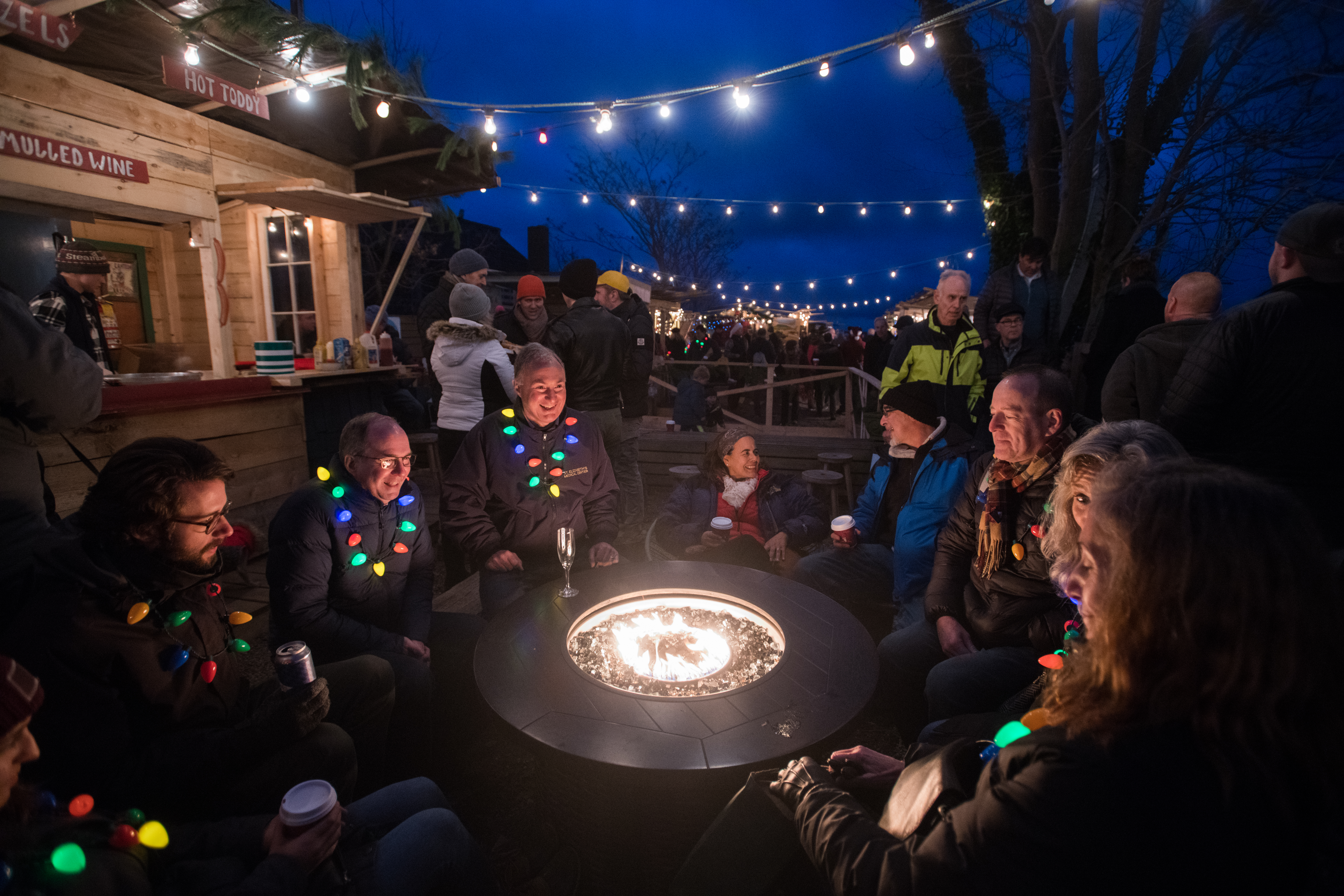 A group of people surround a fire pit at night, each wearing a light-up holiday lights necklace. There are string lights above and a holiday market in the background. A wooden chalet advertises hot toddies and more.