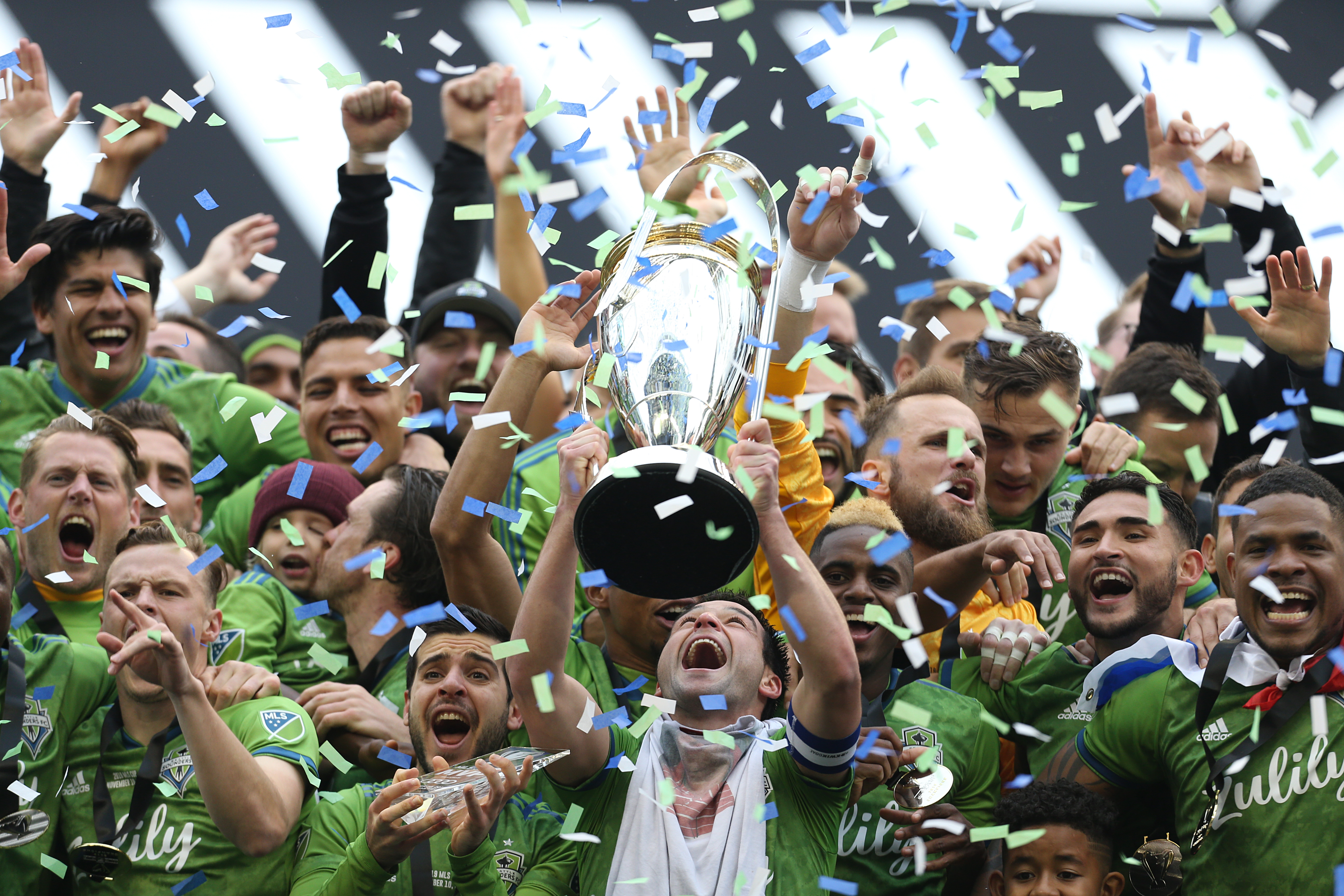 The Seattle Sounders team celebrates their MLS Cup victory among a confetti shower by hoisting the trophy.
