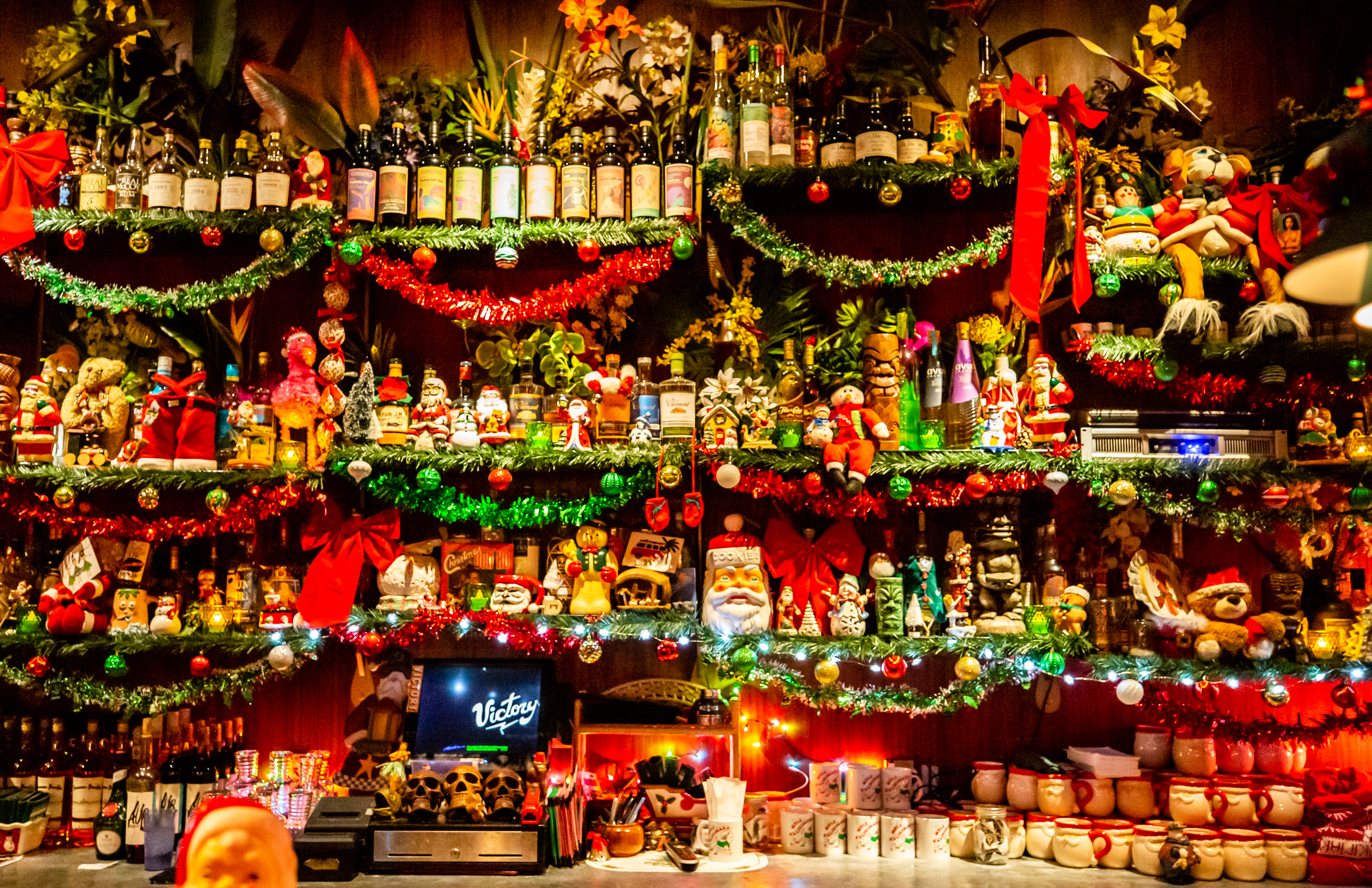 SOS Tiki Bar's back bar filled with bottles, garland, kitschy Santas, toys, and teddy bears