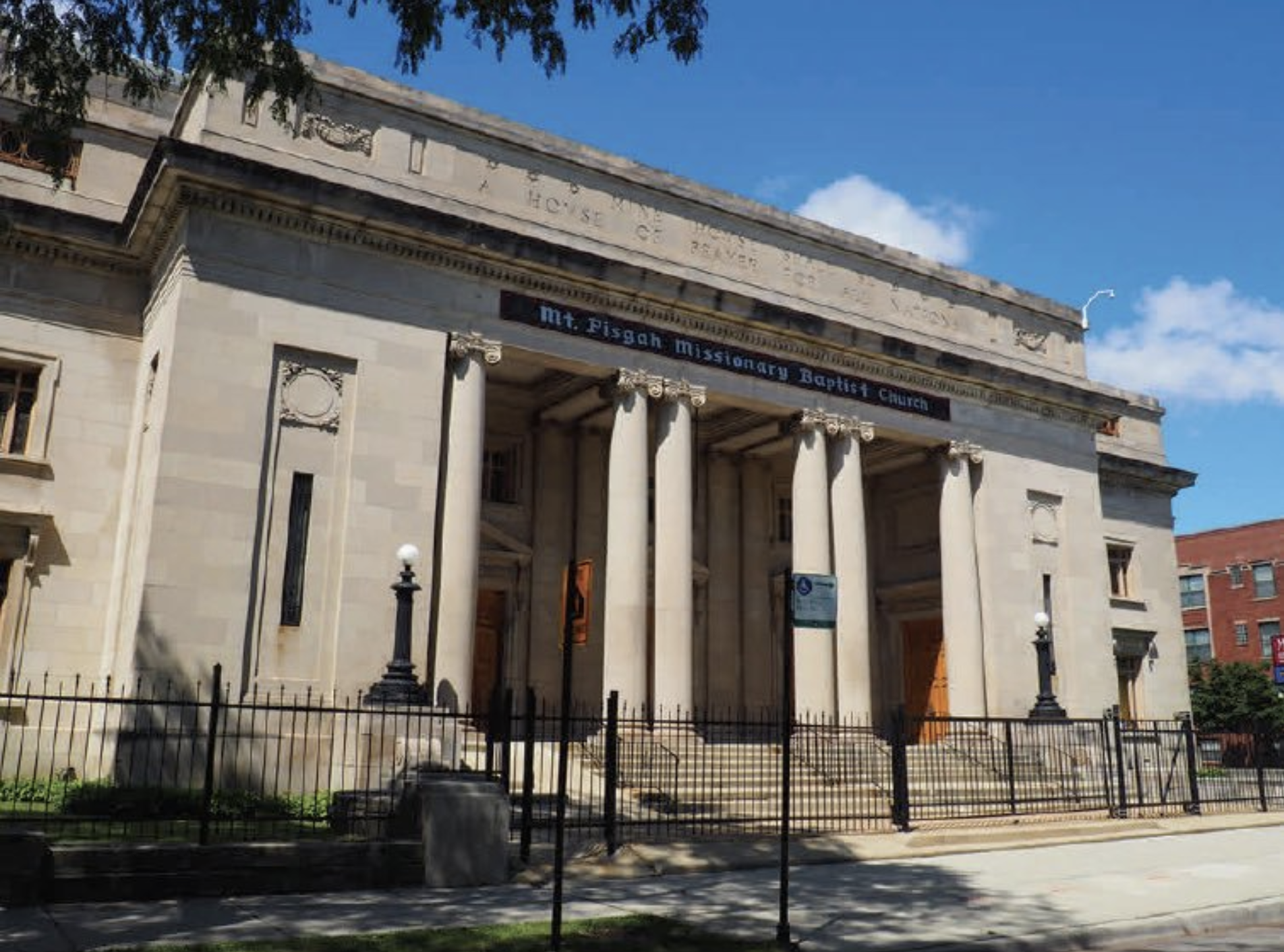 A photo of a large stone building with exterior columns and steps.