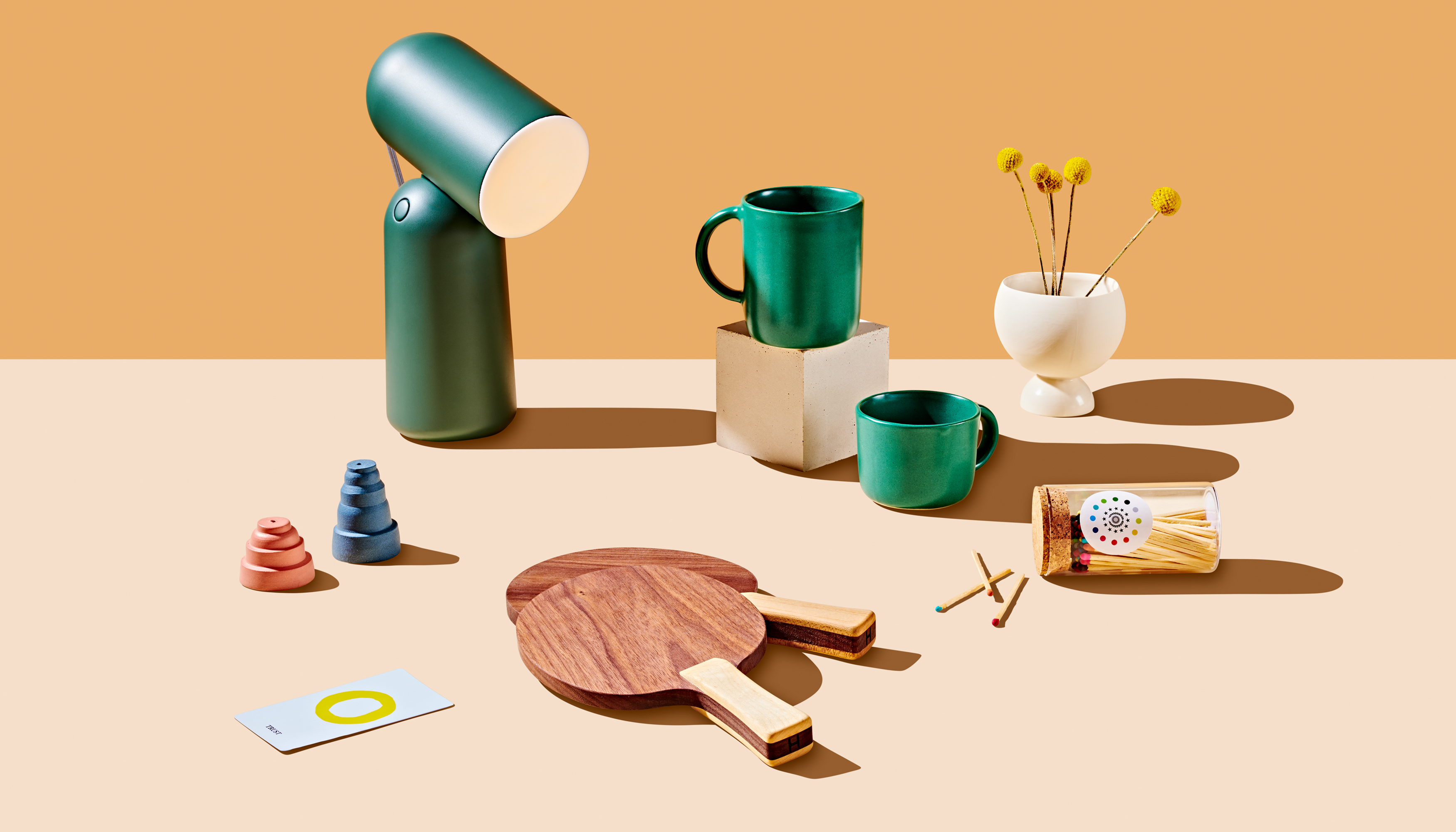 A grouping of objects arranged on a table for the Curbed Holiday Gift Guide 2019. There is a green lamp, wooden ping pong paddles, green cups, salt and pepper shakers, and matches.