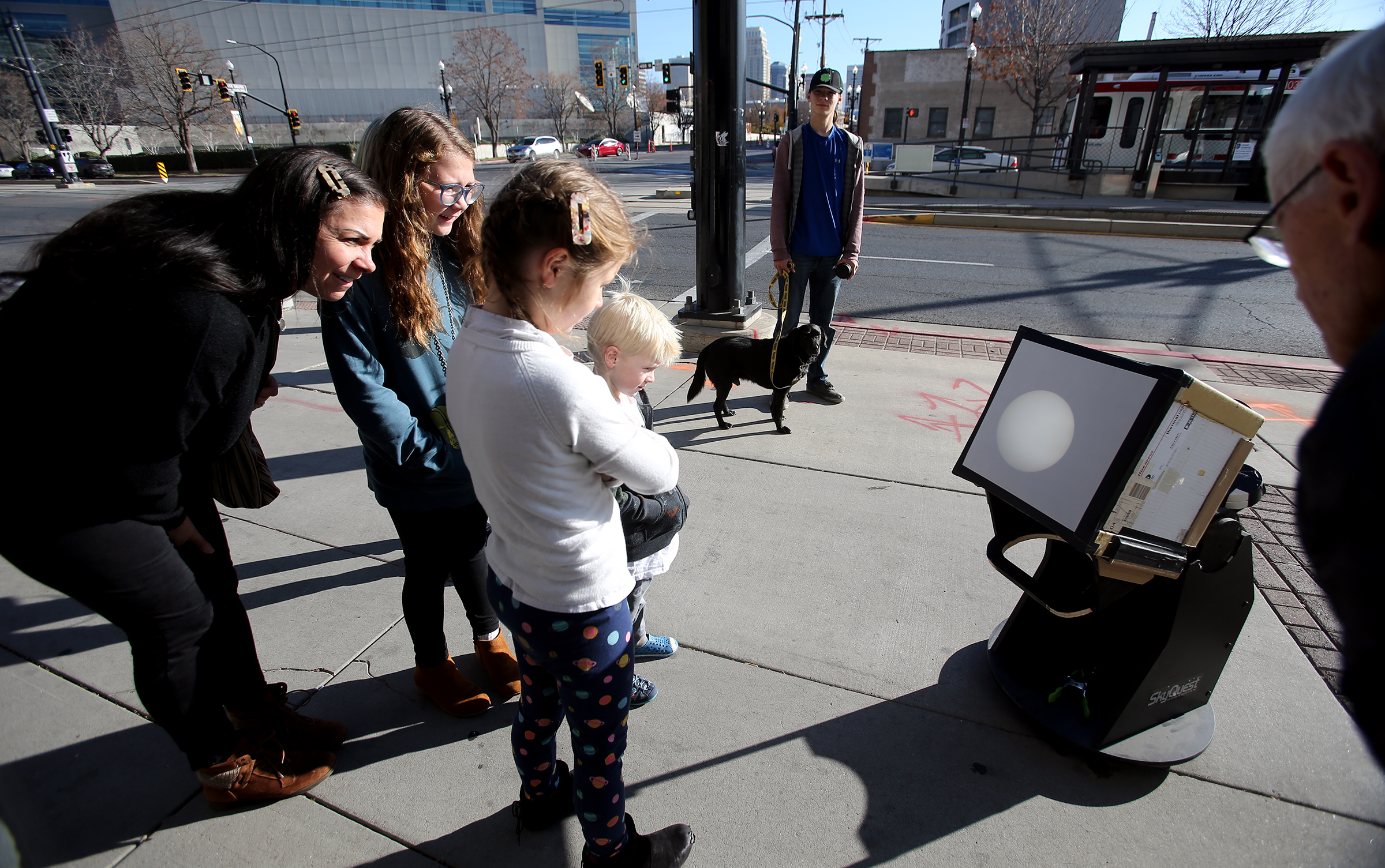 Shauntel Cheney and her children, Annabelle, Lou and Jess, watch as Mercury passes across the sun during a viewing event at the Clark Planetarium in Salt Lake City on Monday, Nov. 11, 2019.