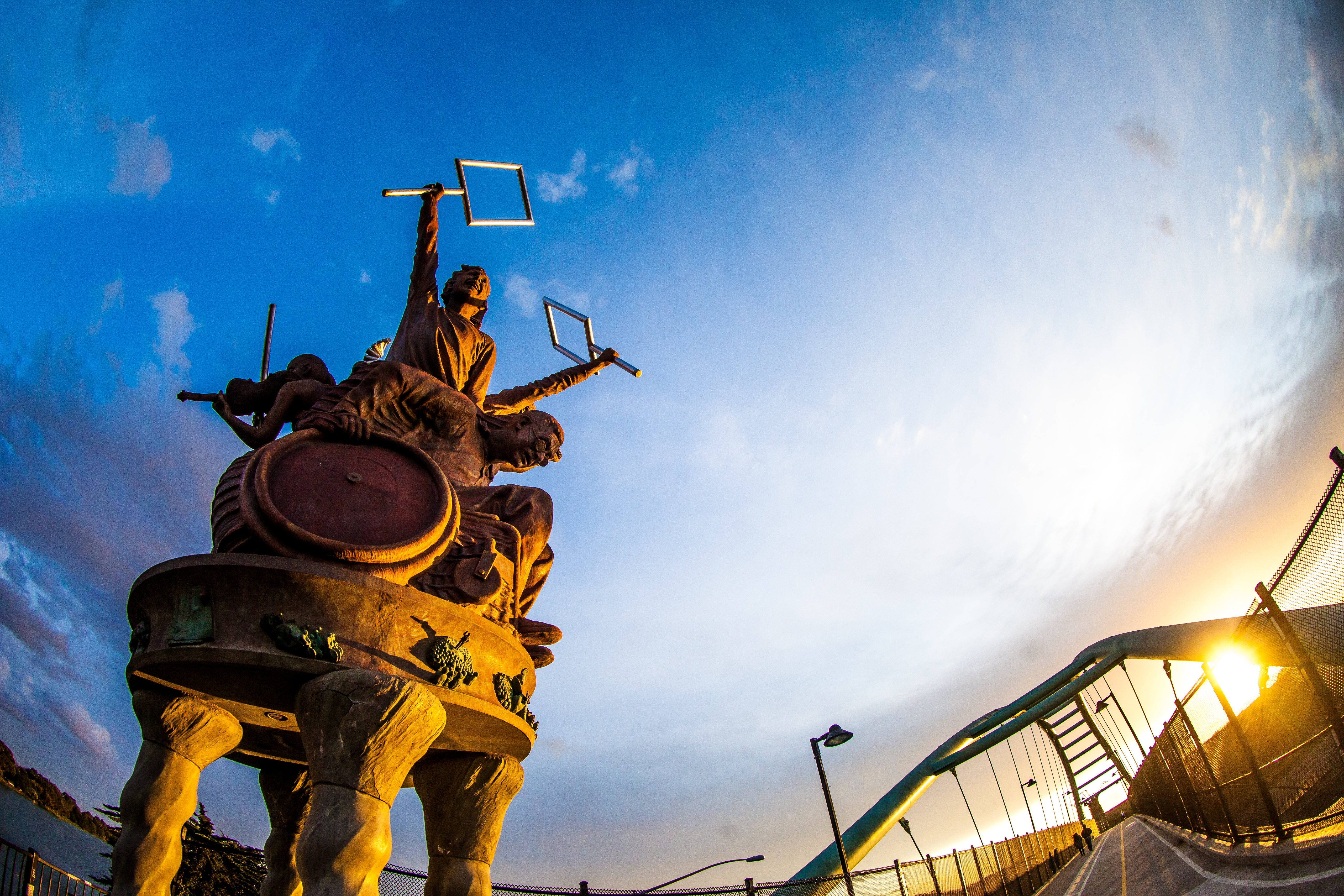 A blue sky highlights a massive reddish sculpture featuring characters protesting.
