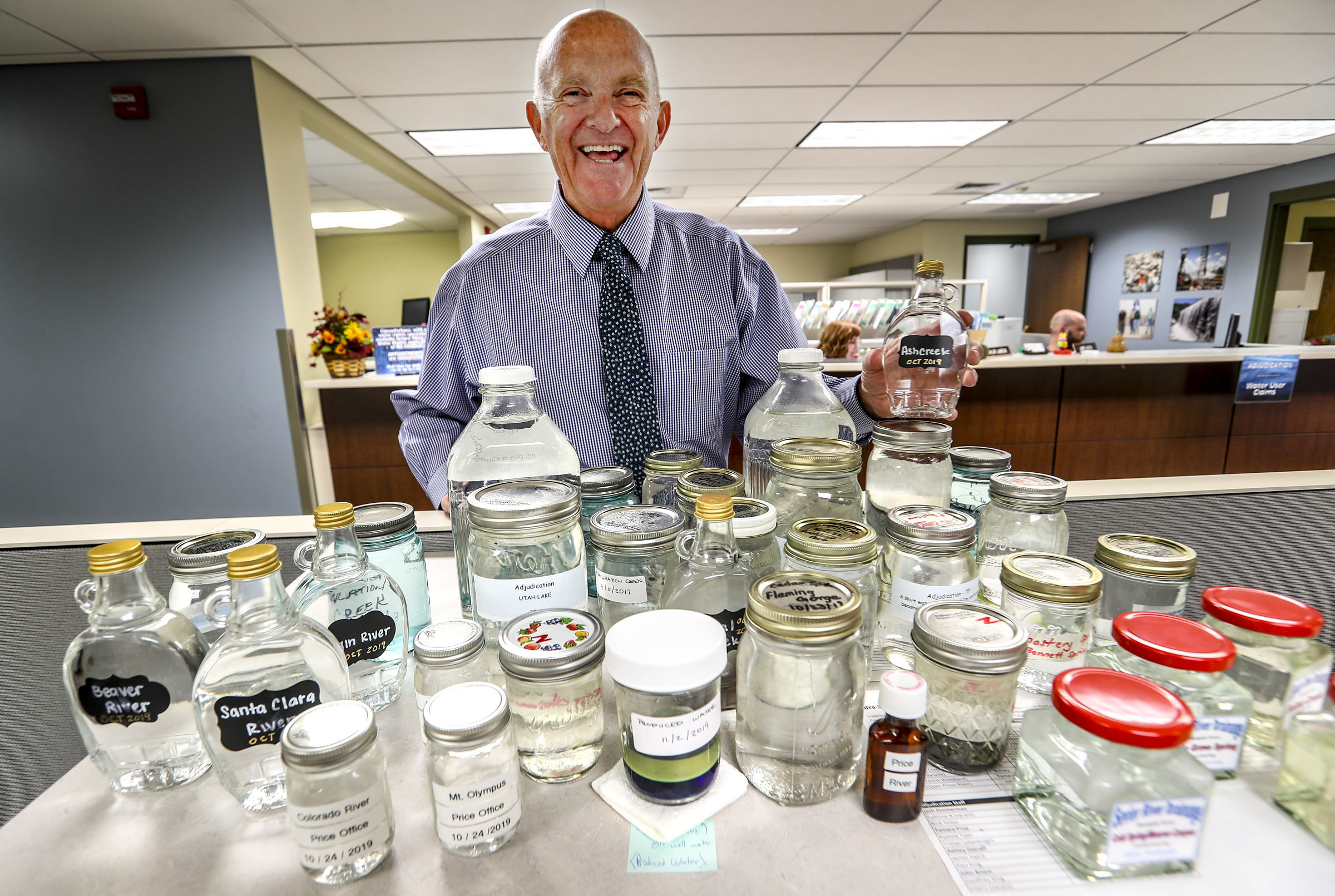 Utah State Engineer Kent Jones laughs as he holds samples of water from areas in the state where water rights were adjudicated. The samples were given to him by fellow employees at his retirement party at the Department of Natural Resources in Salt Lake City on Thursday, Nov. 7, 2019. Jones is retiring from his position this month.