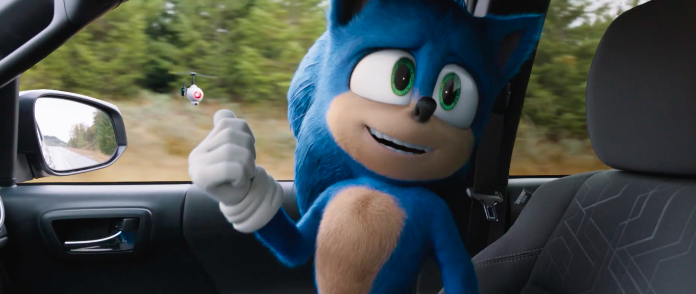 sonic the hedgehog redesigned looks at a drone floating outside a car window