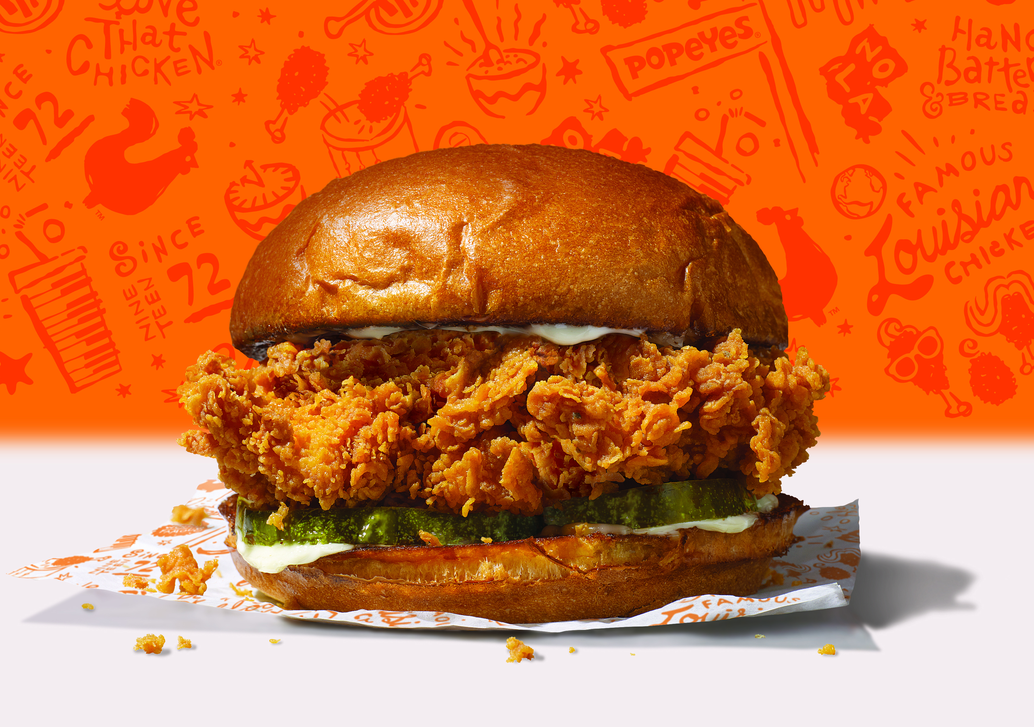 A fried chicken sandwich with a red background