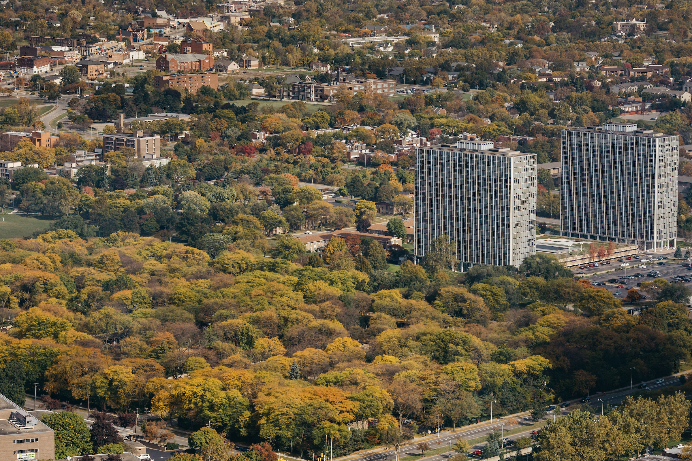 An aerial view of a large, tree-filled park. Two metal towers rise on the right side.