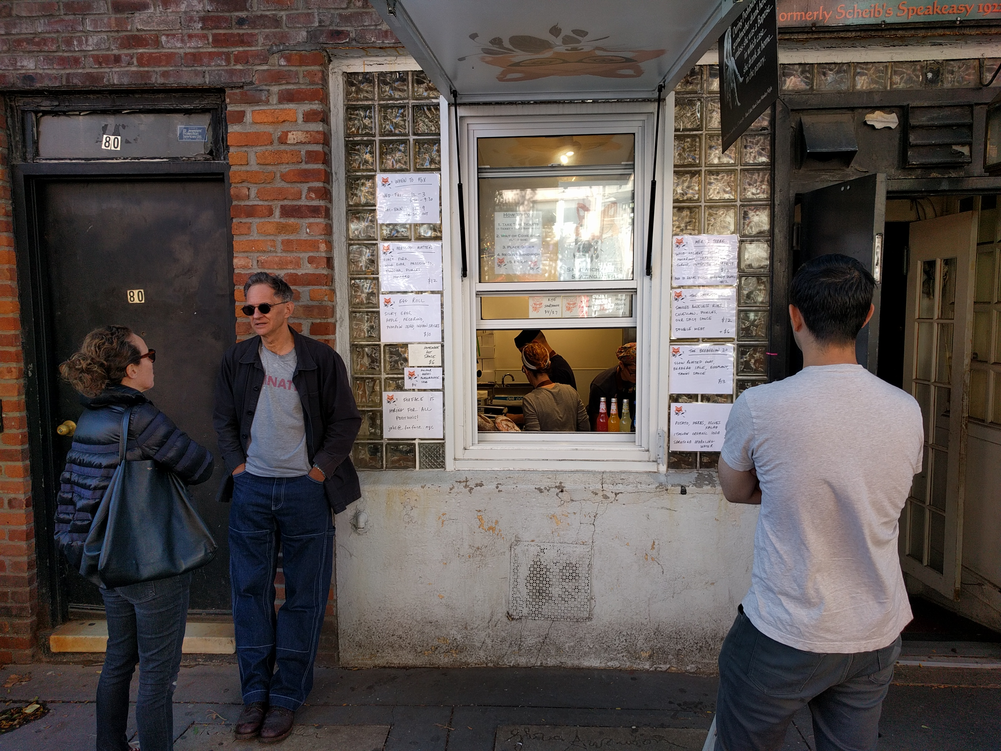 A brick storefront with a window that looks into a kitchen in which cooks can be seen, and a few customer mill around outside...