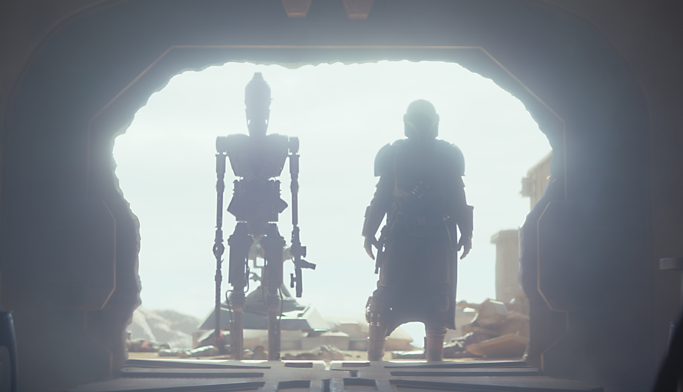 ig-11 and the mandolorian enter a sealed room with the sun at their backs