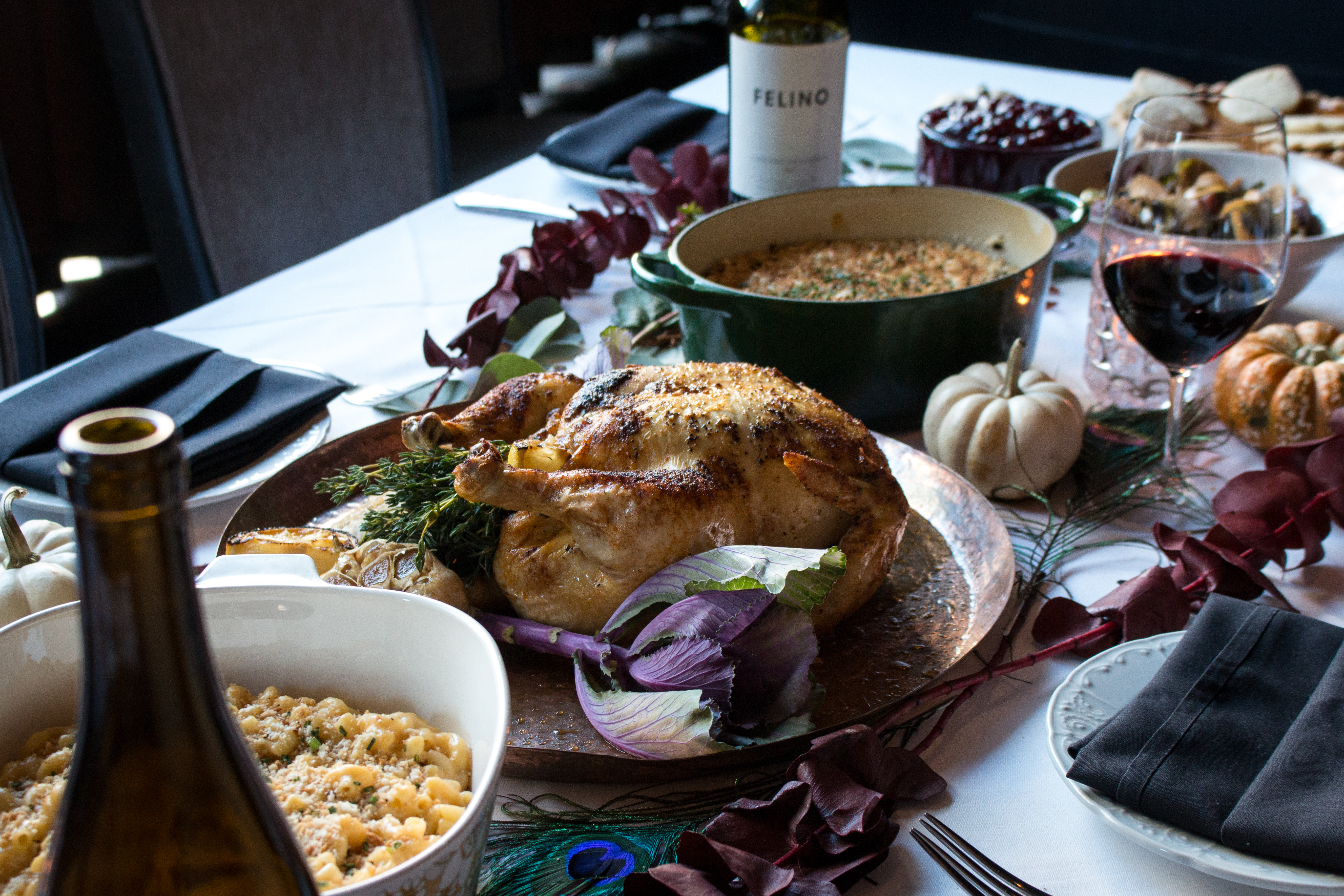 A table with a roasted turkey and bottles of wine.