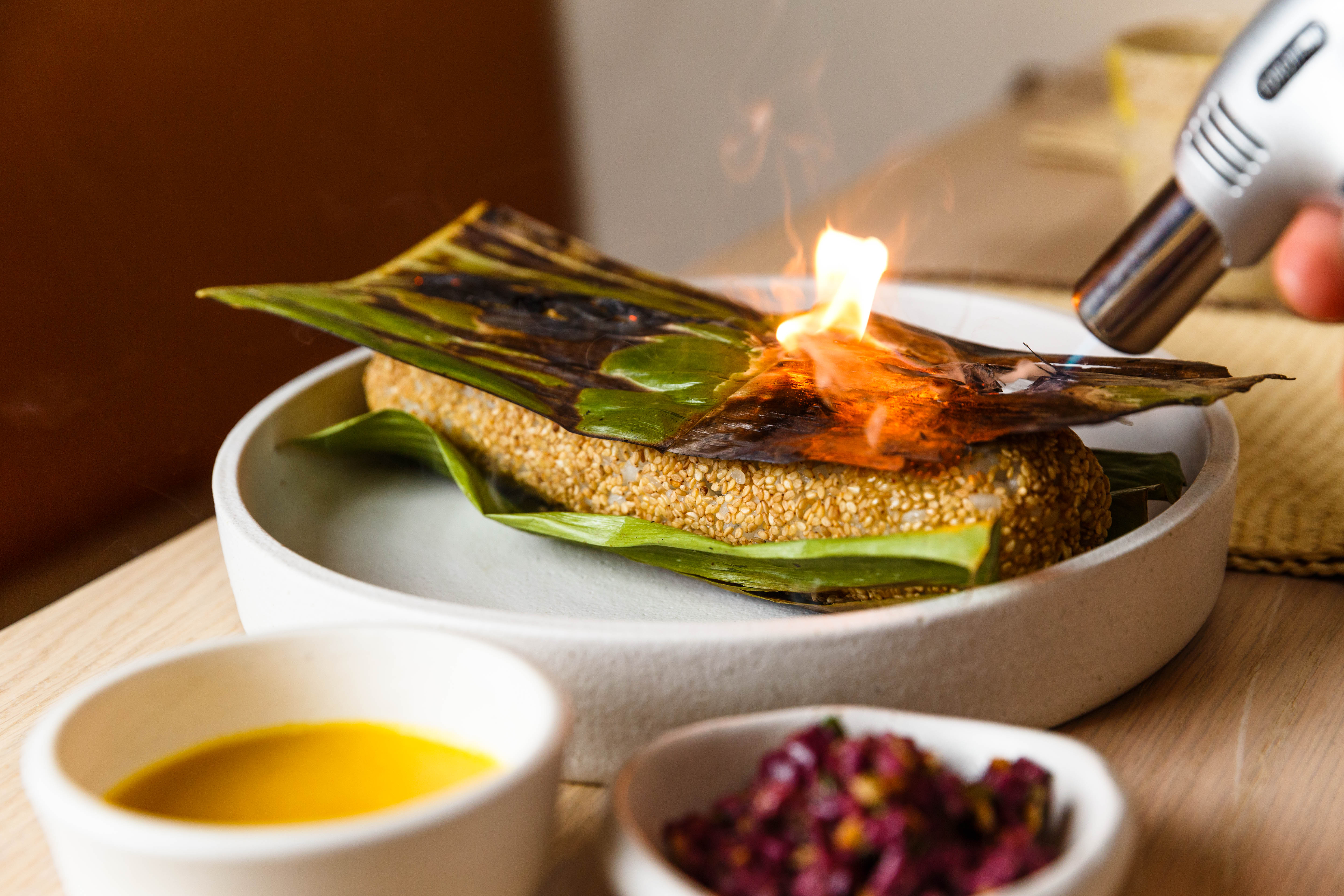 A torch lighting up a green banana leaf placed on top of a burrito-like roll