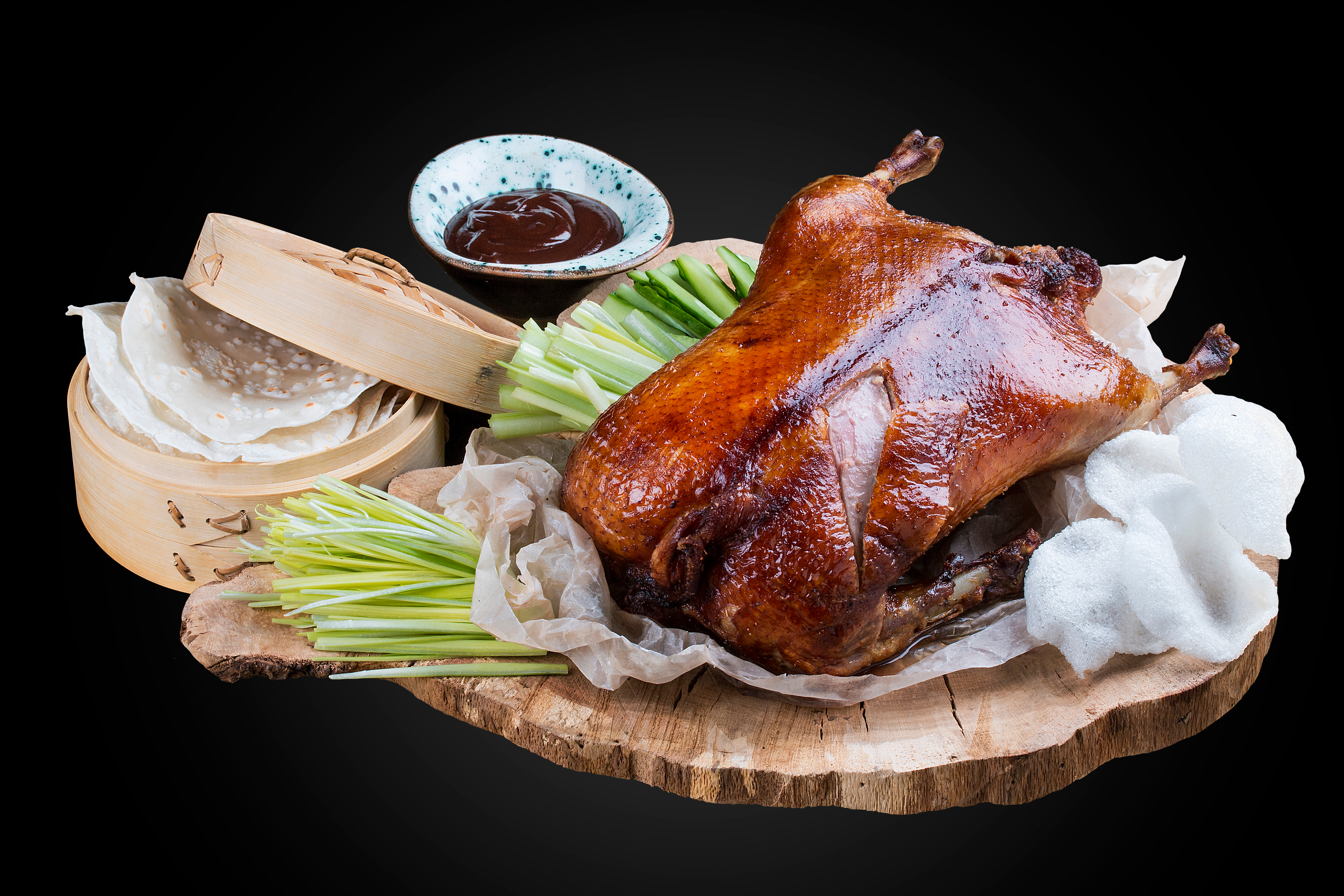 A stock photography of a glossy, dark Peking duck on a wooden platter on a black background, surrounded by accoutrements like Hoisin sauce and a wooden steamer basket of pancakes.