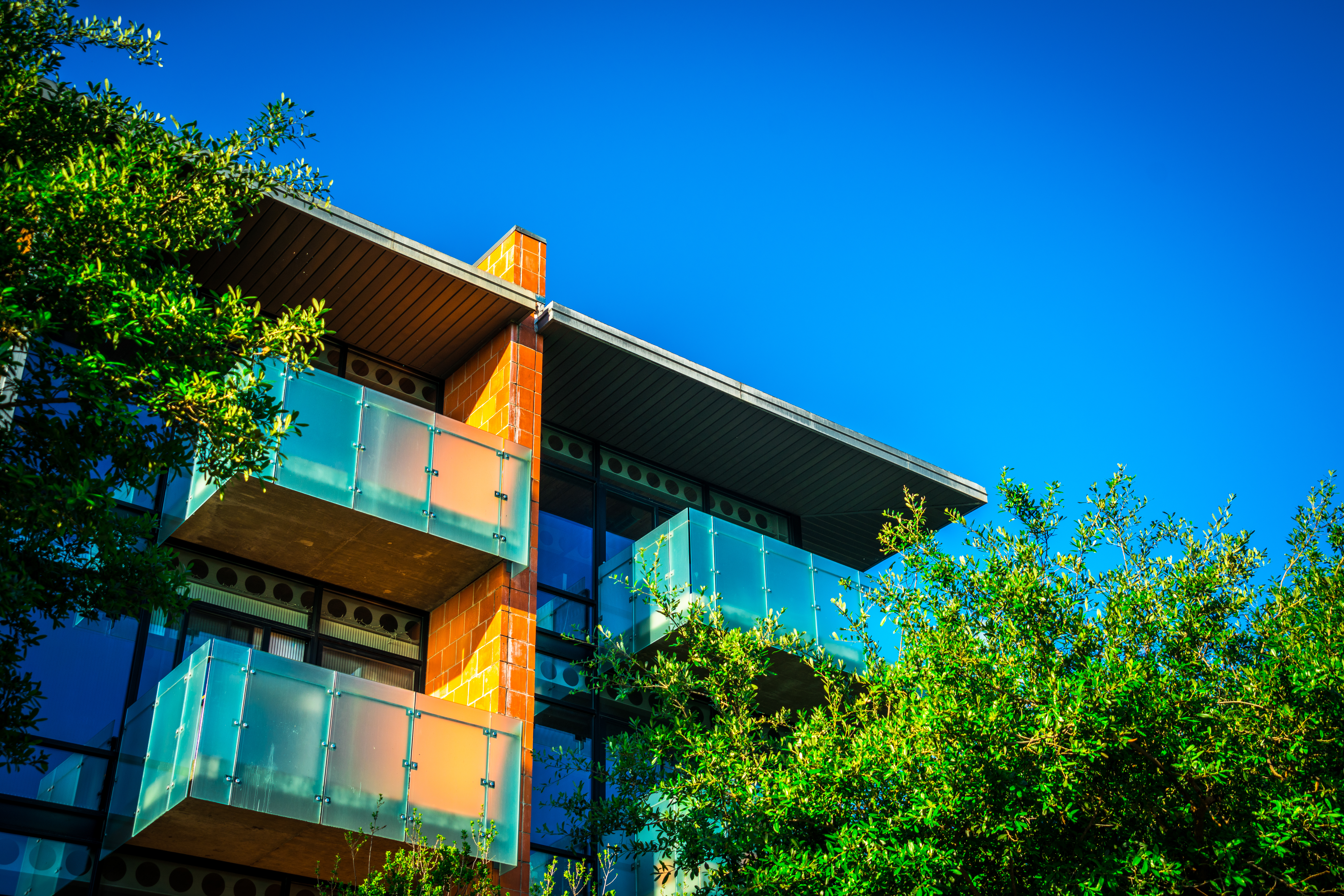 Upward-angled photograph of the top corner of a contemporary apartment building. The apartments have balconies with perforated steel railings, with a vertical brick wall dividing them. There's a blue sky in the background and leafy trees in front.