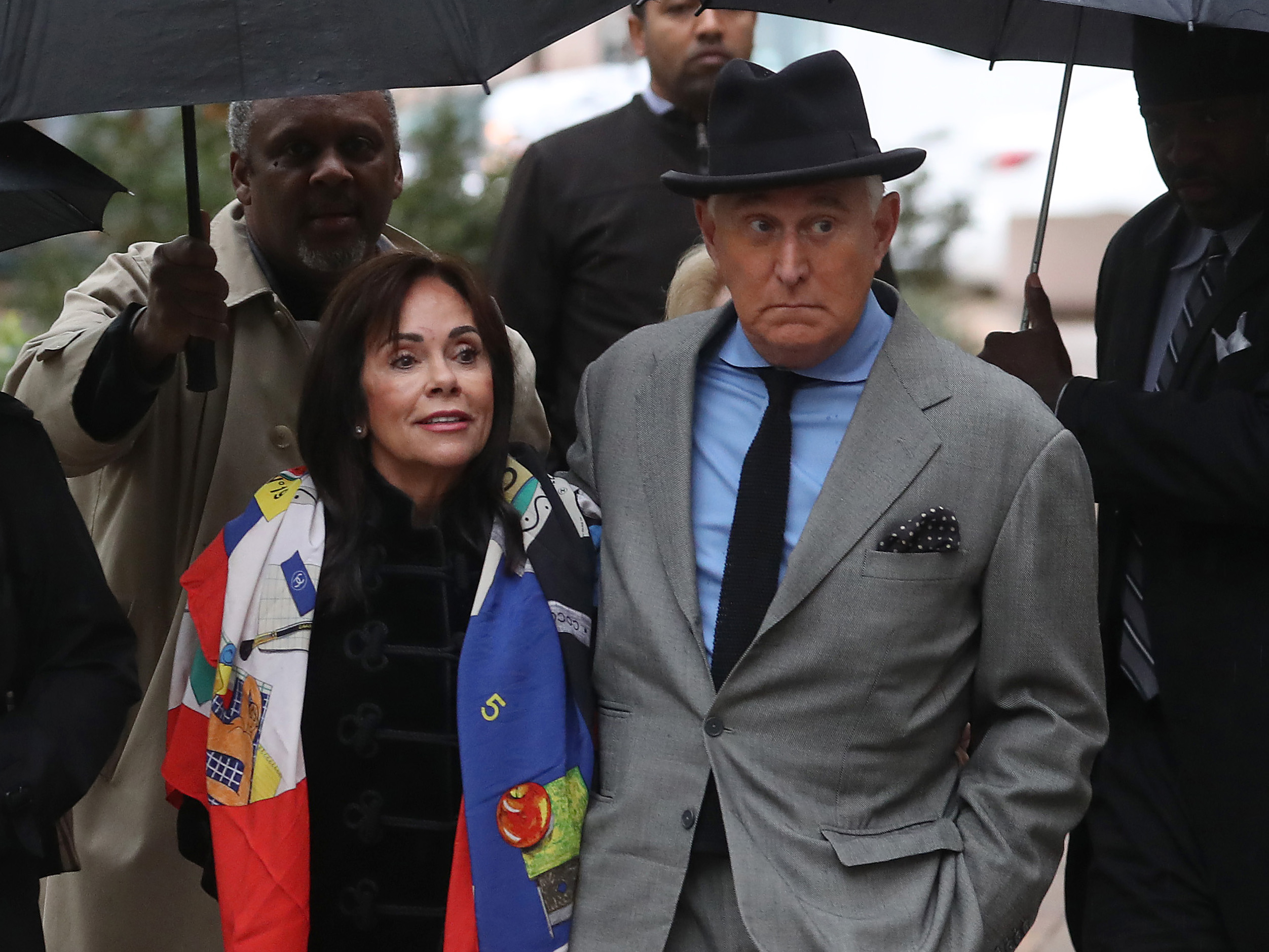 Roger Stone, the former adviser to President Donald Trump, stands outside with his wife Nydia Stone while people around them hold up umbrellas.