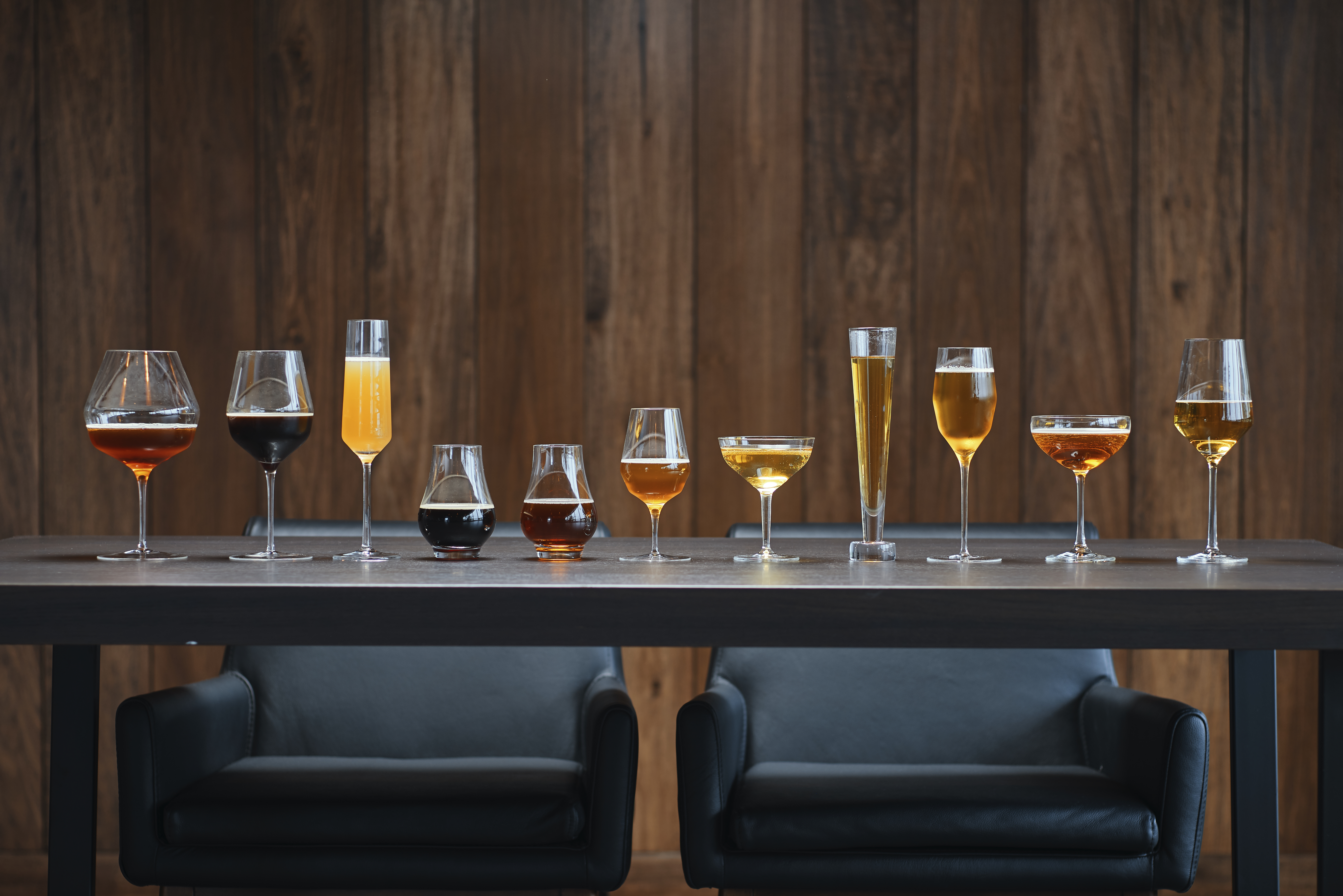 A wooden table with a handful of different beers lines up.