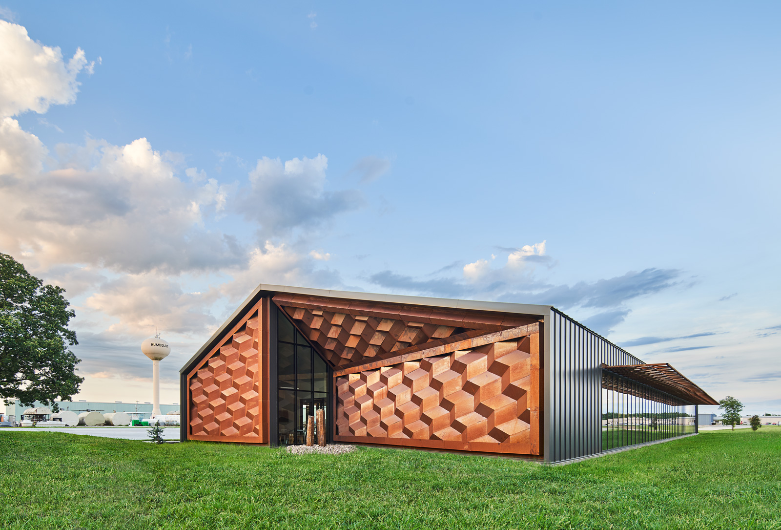 A modern building with a gabled roof and gray metal facade. The ends of the building are clad in rust-toned metal that looks like a raised checkerboard pattern.