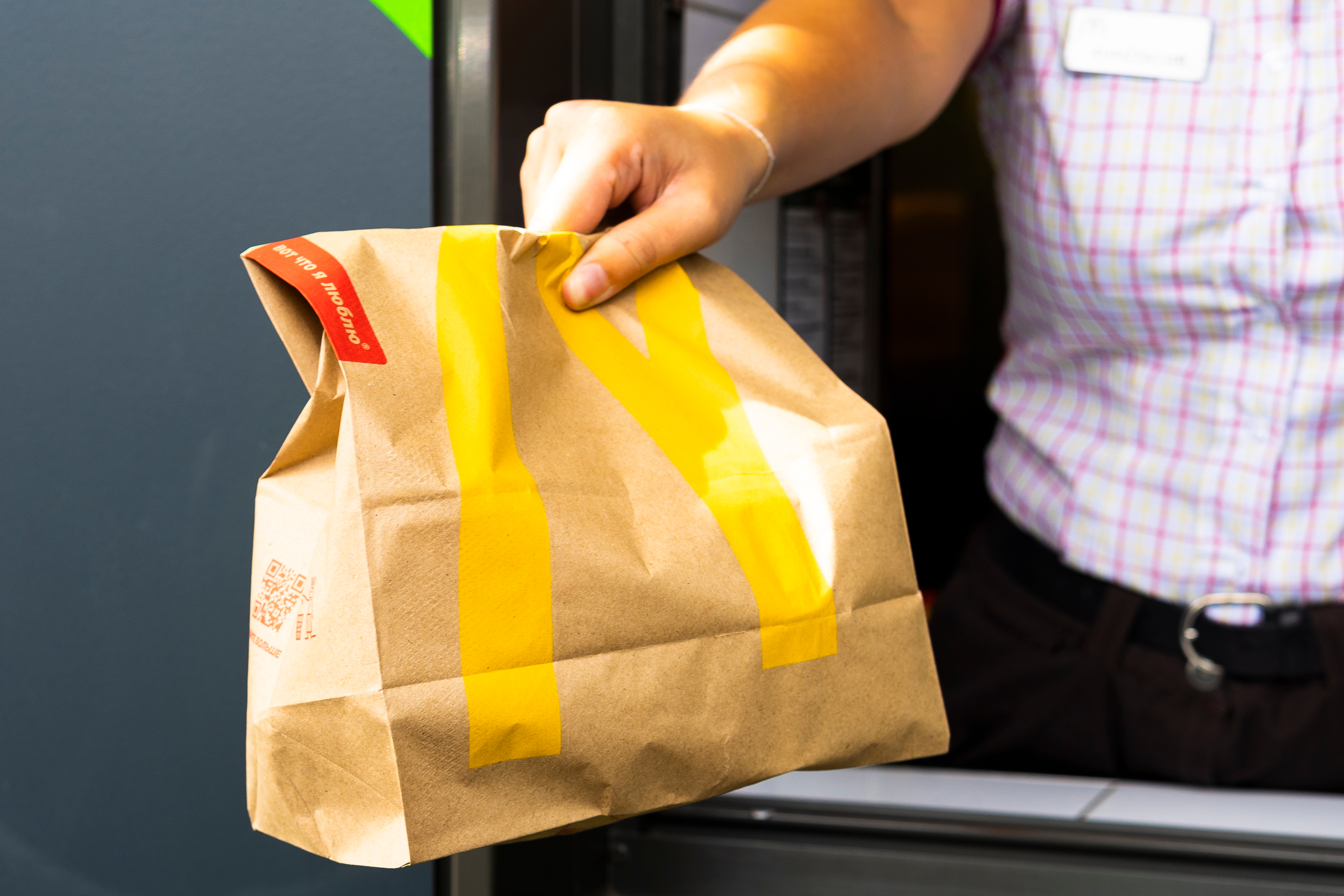 The torso of a McDonald's employee in a pink checkered shirt, passing a bag of food labeled with McDonald's branding through the drive-thru window.