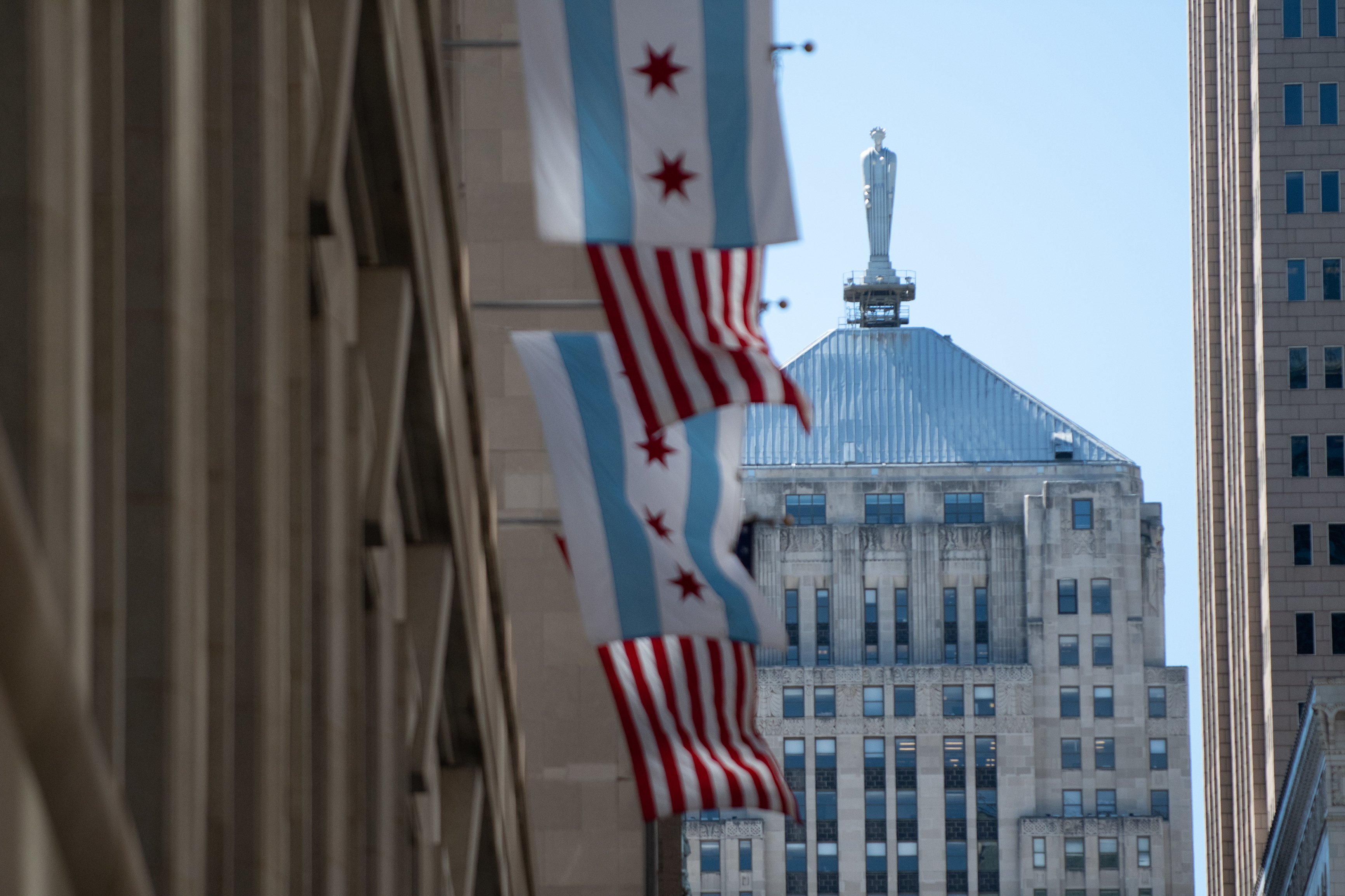 The Chicago and United States of America flags fly outside City Hall with the Chicago Board of Trade building in the background.